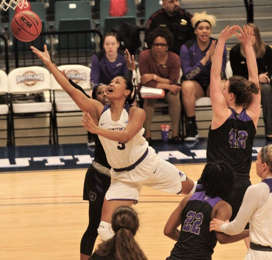 ACU's Dominique Golightly (3) splits two defenders as she drives to the basket in the first quarter.
