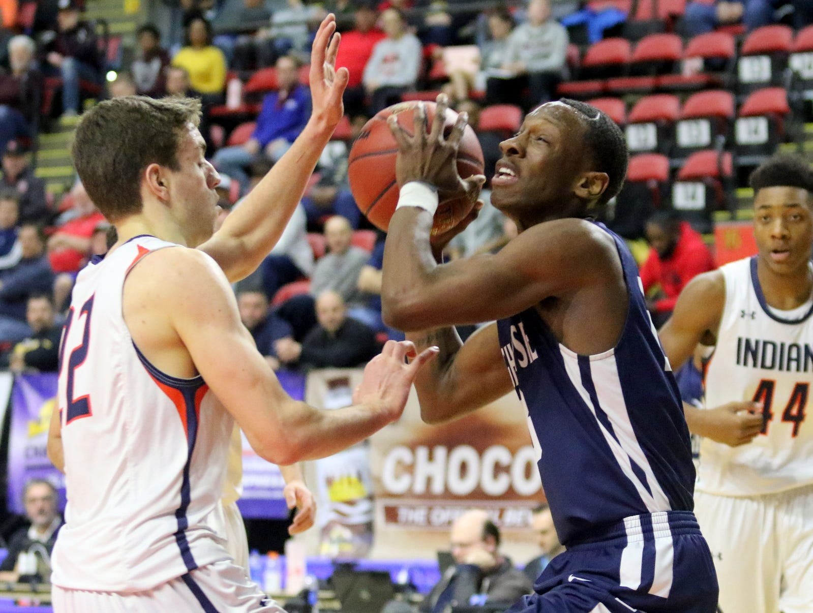 Jaquan Pearson of Poughkeepsie looks for room as Thomas Santella of Manhasset defends during a Class A boys basketball state semifinal March 15, 2019 at Floyd L. Maines Veterans Memorial Arena in Binghamton.