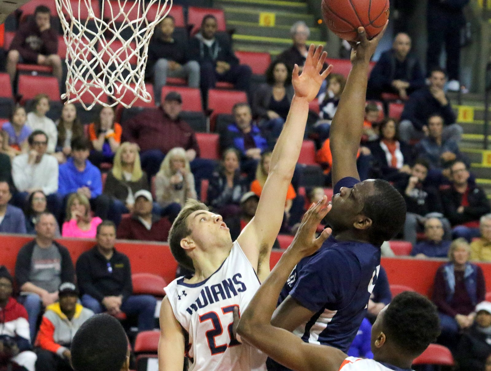 Tremell Reaves of Poughkeepsie takes a shot as Thomas Santella of Manhasset defends during a Class A boys basketball state semifinal March 15, 2019 at Floyd L. Maines Veterans Memorial Arena in Binghamton.