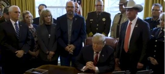 Brevard County Sheriff Wayne Ivey, second from right, joins President Trump on Friday at the Oval Office to witness Trump's signing of his veto.
