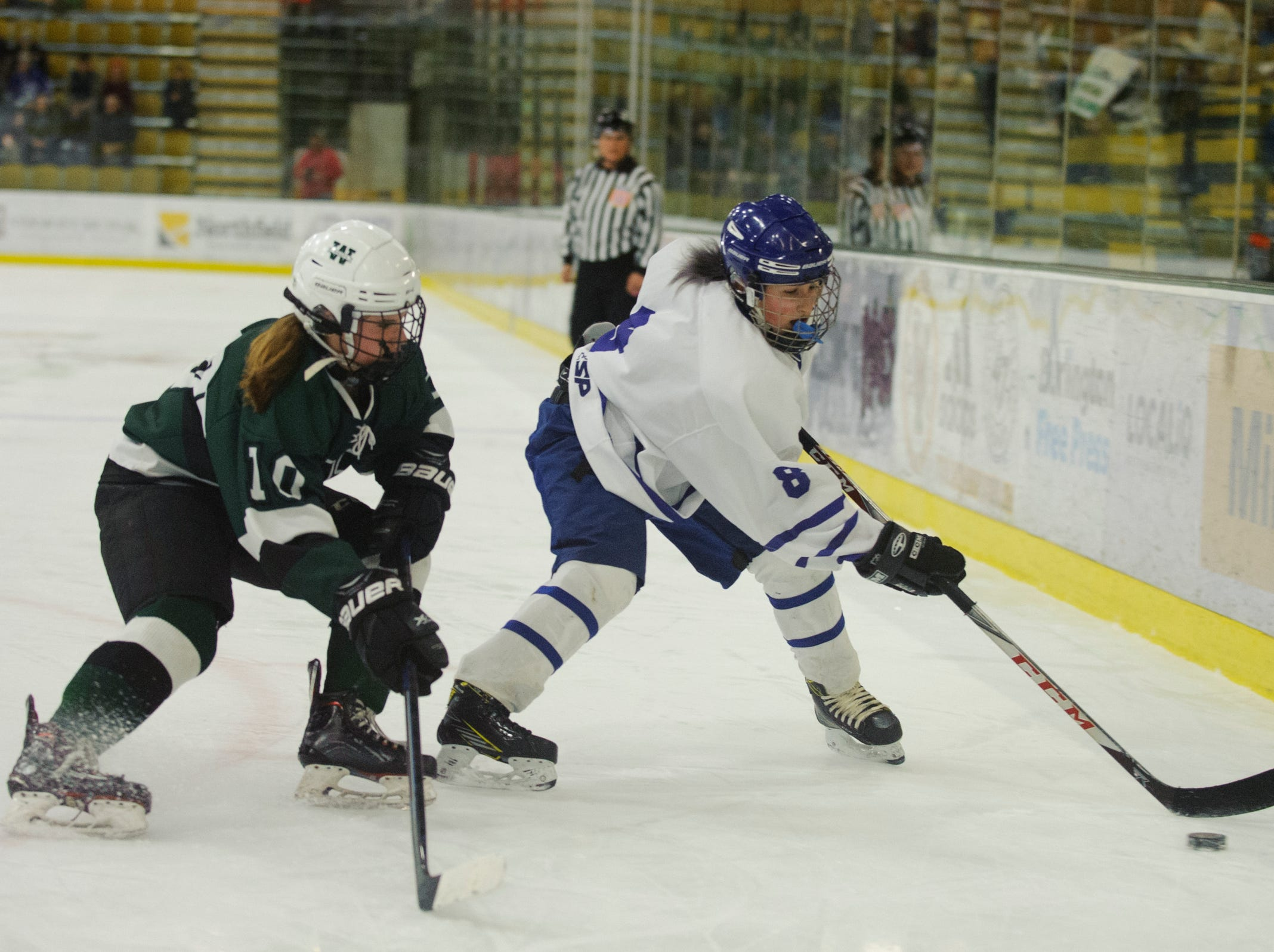 Missisquoi's Kaley Stefaniak (8) skates past Woodstock's Allie Cimis (10) with the puck during the DII girls hockey championship game between the Woodstock Wasps and the Missisquoi Thunderbirds at Gutterson Field House on Thursday night March 14, 2019 in Burlington, Vermont.