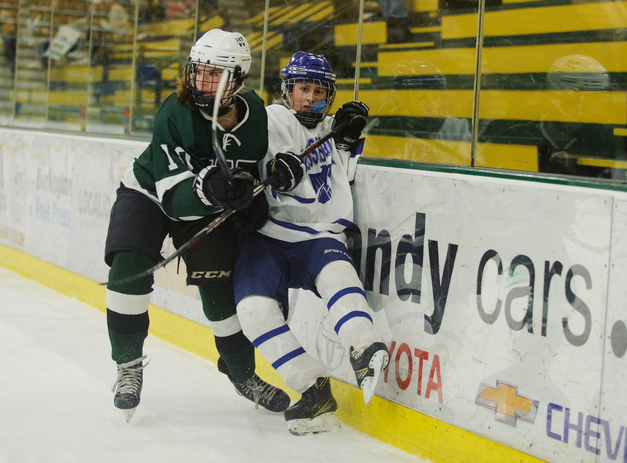 Woodstock's Allie Cimis (10)  checks Missisquoi's Kaley Stefaniak (8) into the boards during the DII girls hockey championship game between the Woodstock Wasps and the Missisquoi Thunderbirds at Gutterson Field House on Thursday night March 14, 2019 in Burlington, Vermont.