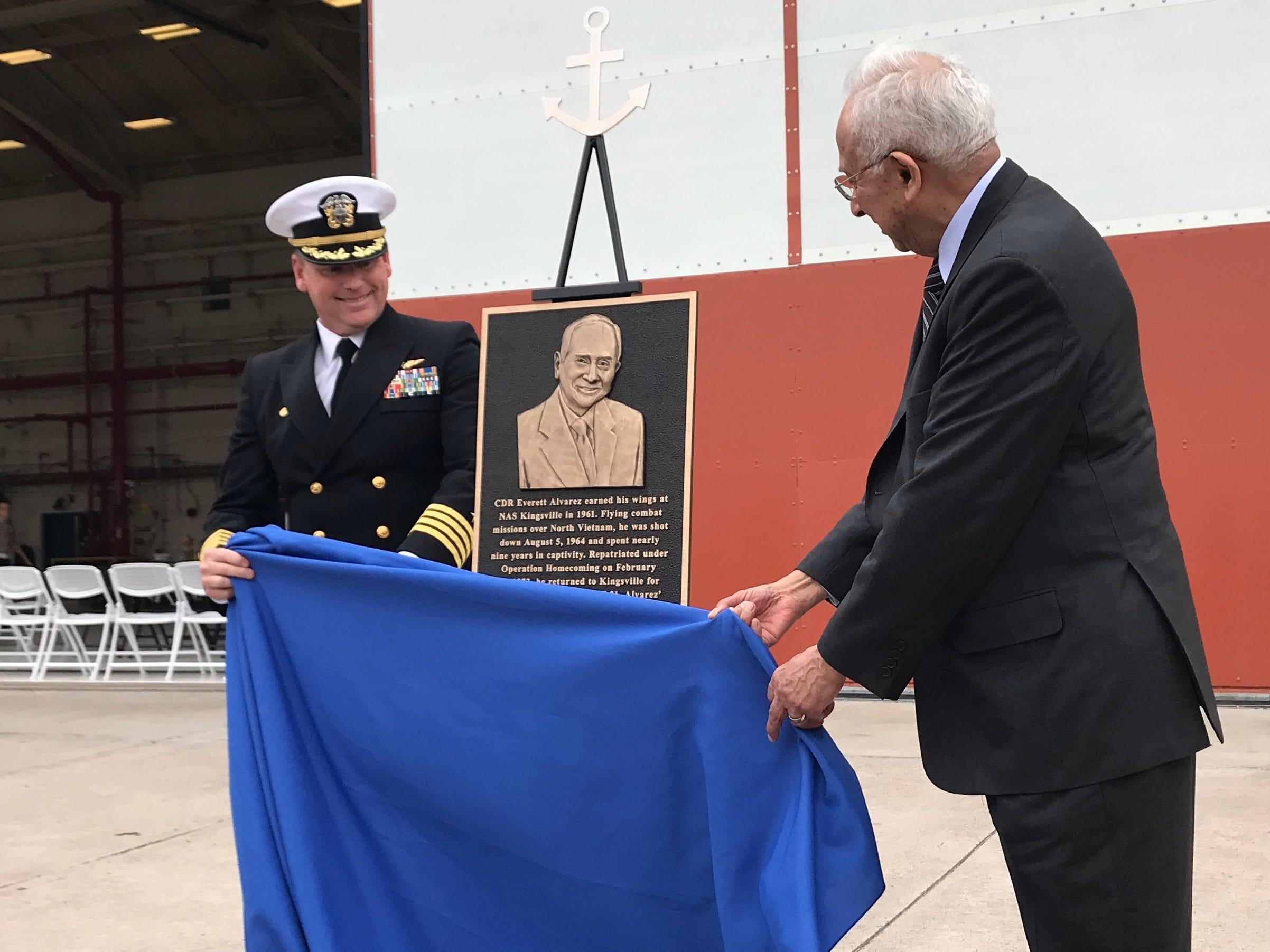 U.S . Navy Capt. Erik A. Spitzer, Commanding Officer of Naval Air Station Kingsville, (left) and retired Commander Everett Alvarez Jr. reveal a plaque. The plaque designates naming a hangar after Alvarez on Thursday, March 14, 2019, at Naval Air Station Kingsville.