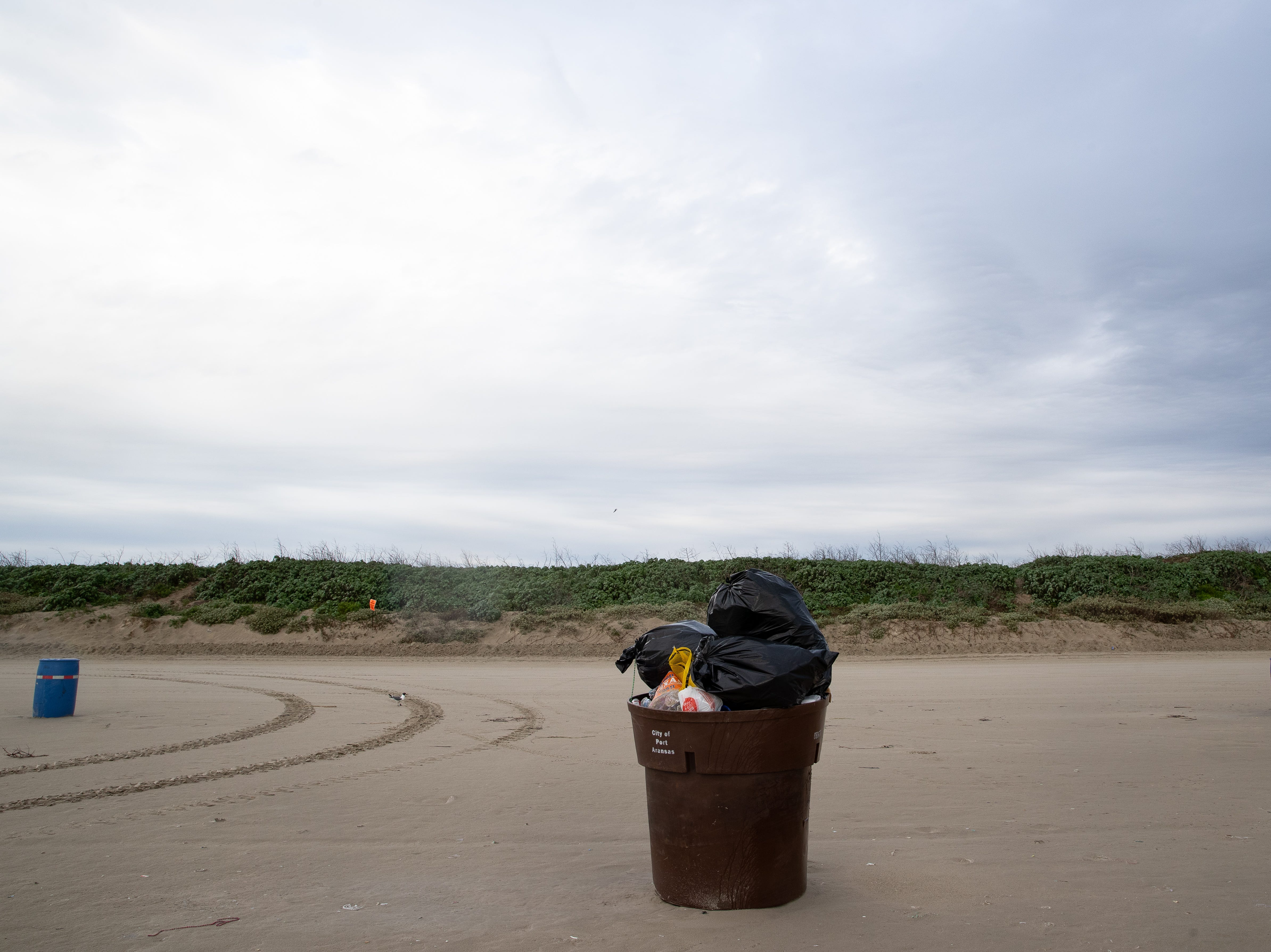 A over flowing trash container sits on the beach in Port Aransas in the early morning during the week of spring break on Friday, March 15, 2019.