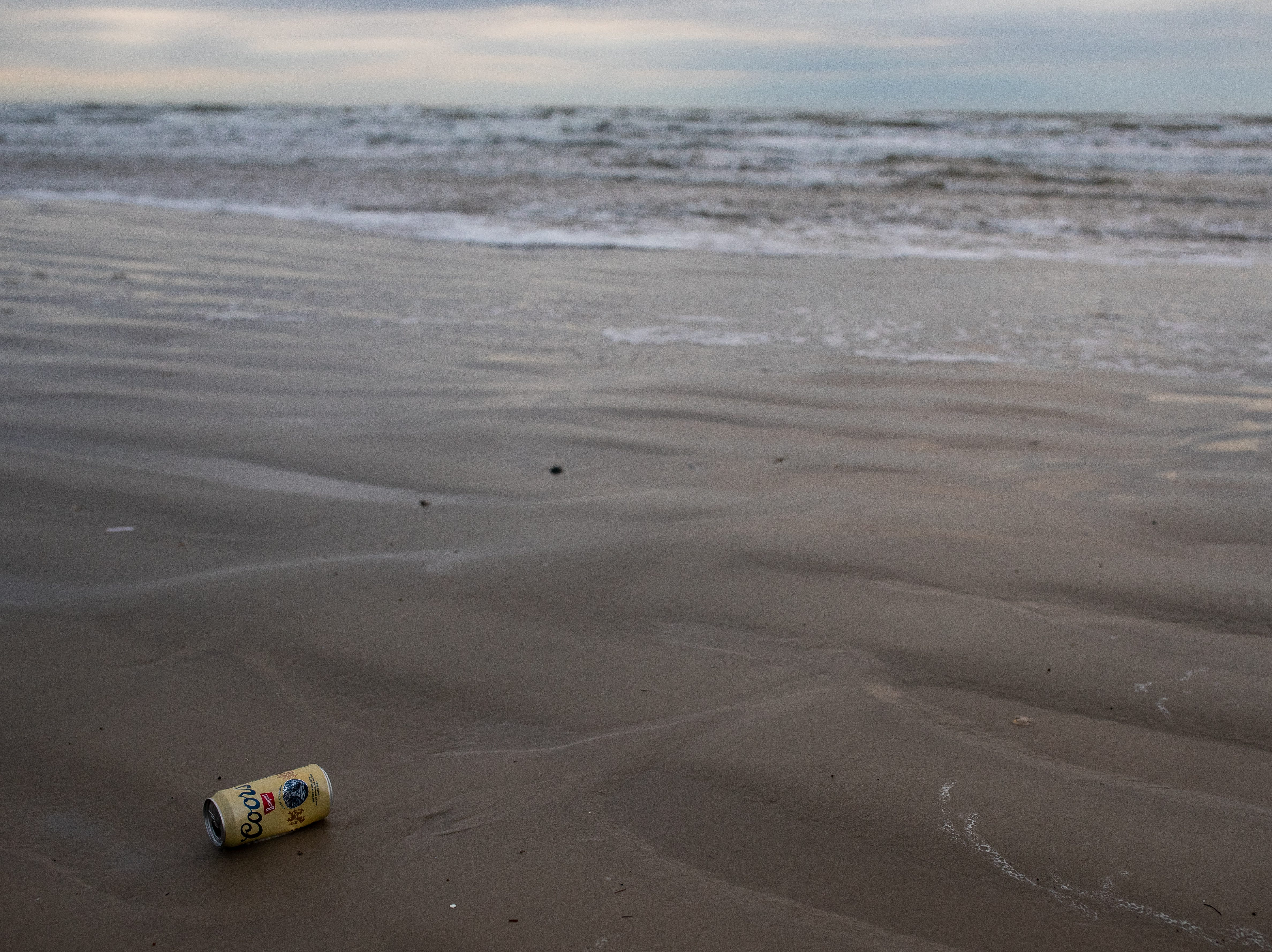 A beer can blows along the beach in Port Aransas, left behind on the beach from the bay before during the week of spring break on Friday, March 15, 2019.