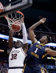 Texas Tech's Norense Odiase (32) gets past West Virginia's Derek Culver (1) for a dunk during the first half of an NCAA college basketball game in the Big 12 men's tournament Thursday, March 14, 2019, in Kansas City, Mo. (AP Photo/Charlie Riedel)