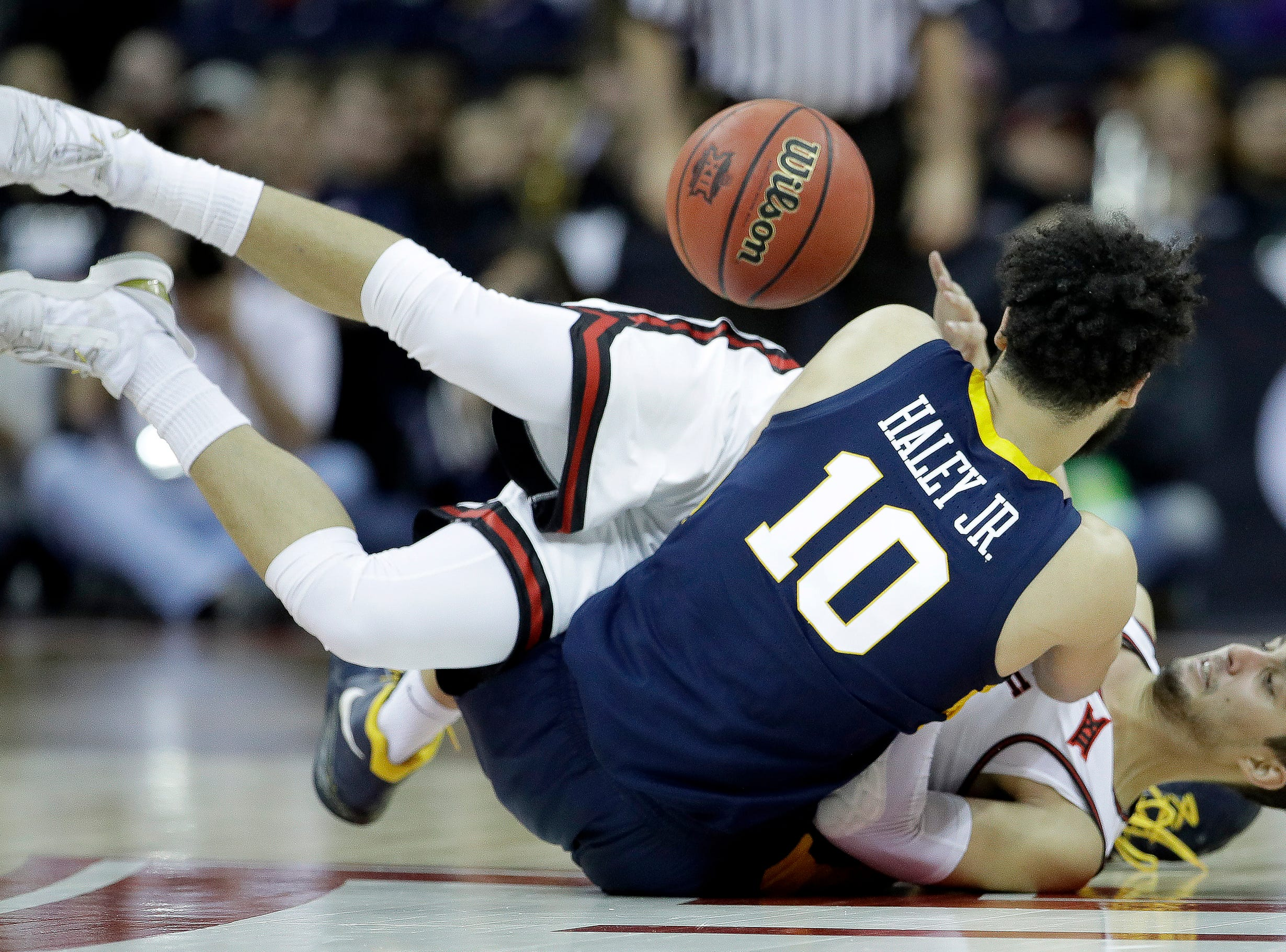 West Virginia's Jermaine Haley (10) and Texas Tech's Davide Moretti battle for the ball during the first half of an NCAA college basketball game in the Big 12 men's tournament Thursday, March 14, 2019, in Kansas City, Mo. (AP Photo/Charlie Riedel)