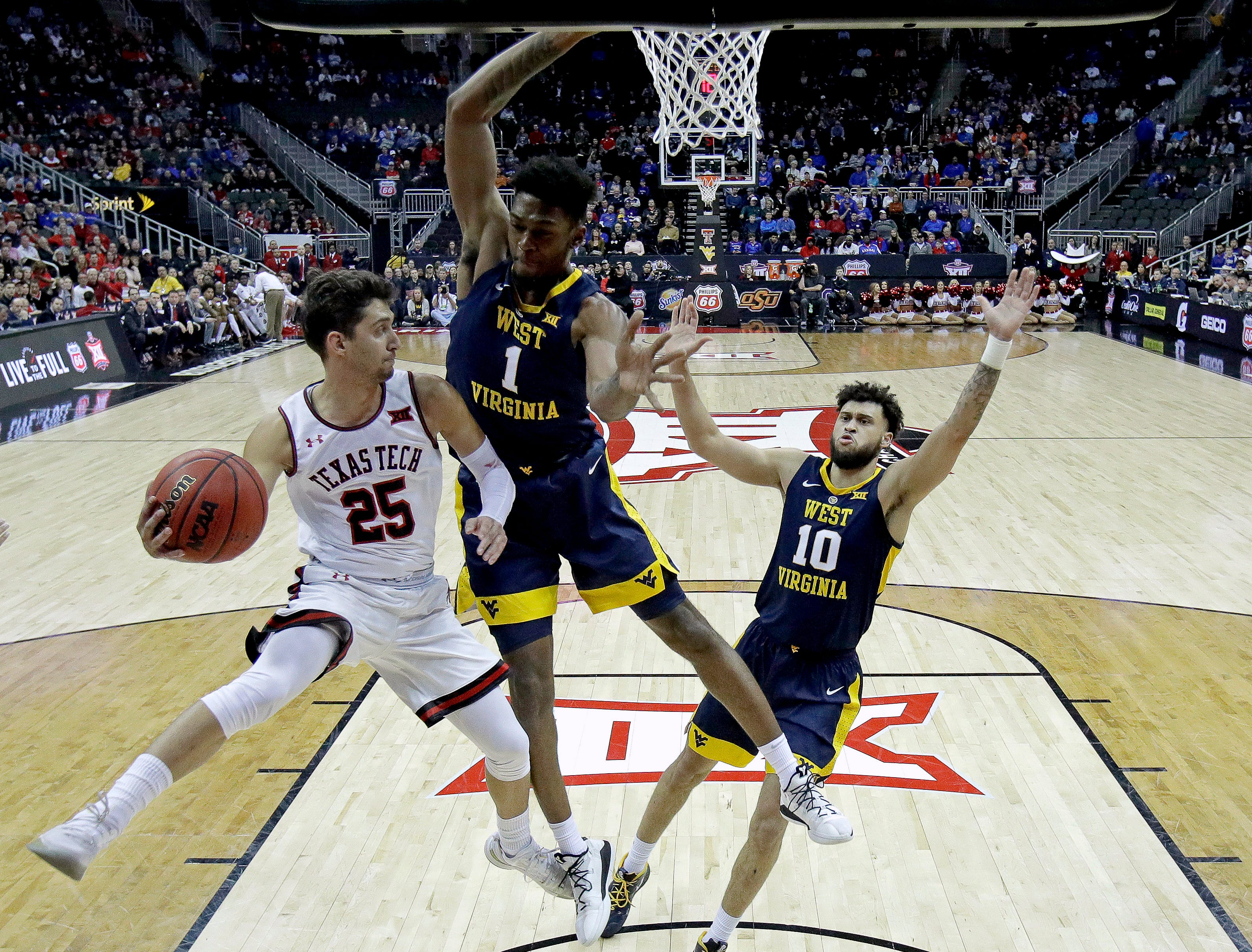 Texas Tech's Davide Moretti (25) passes the ball past West Virginia's Derek Culver (1) during the first half of an NCAA college basketball game in the Big 12 men's tournament Thursday, March 14, 2019, in Kansas City, Mo. (AP Photo/Charlie Riedel)