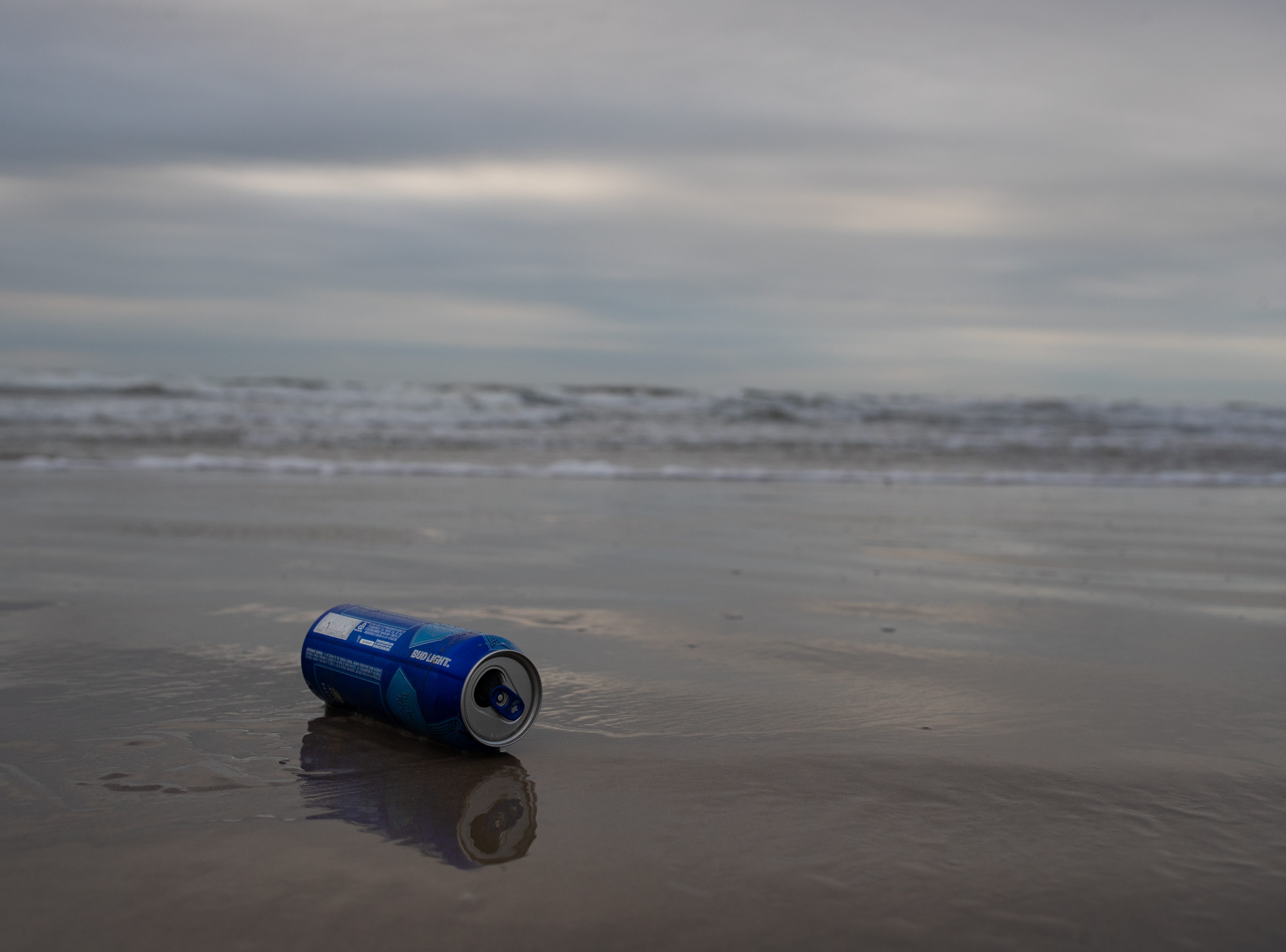 A beer can sits in the surf  on the beach in Port Aransas, left behind on the beach from the bay before during the week of spring break on Friday, March 15, 2019.