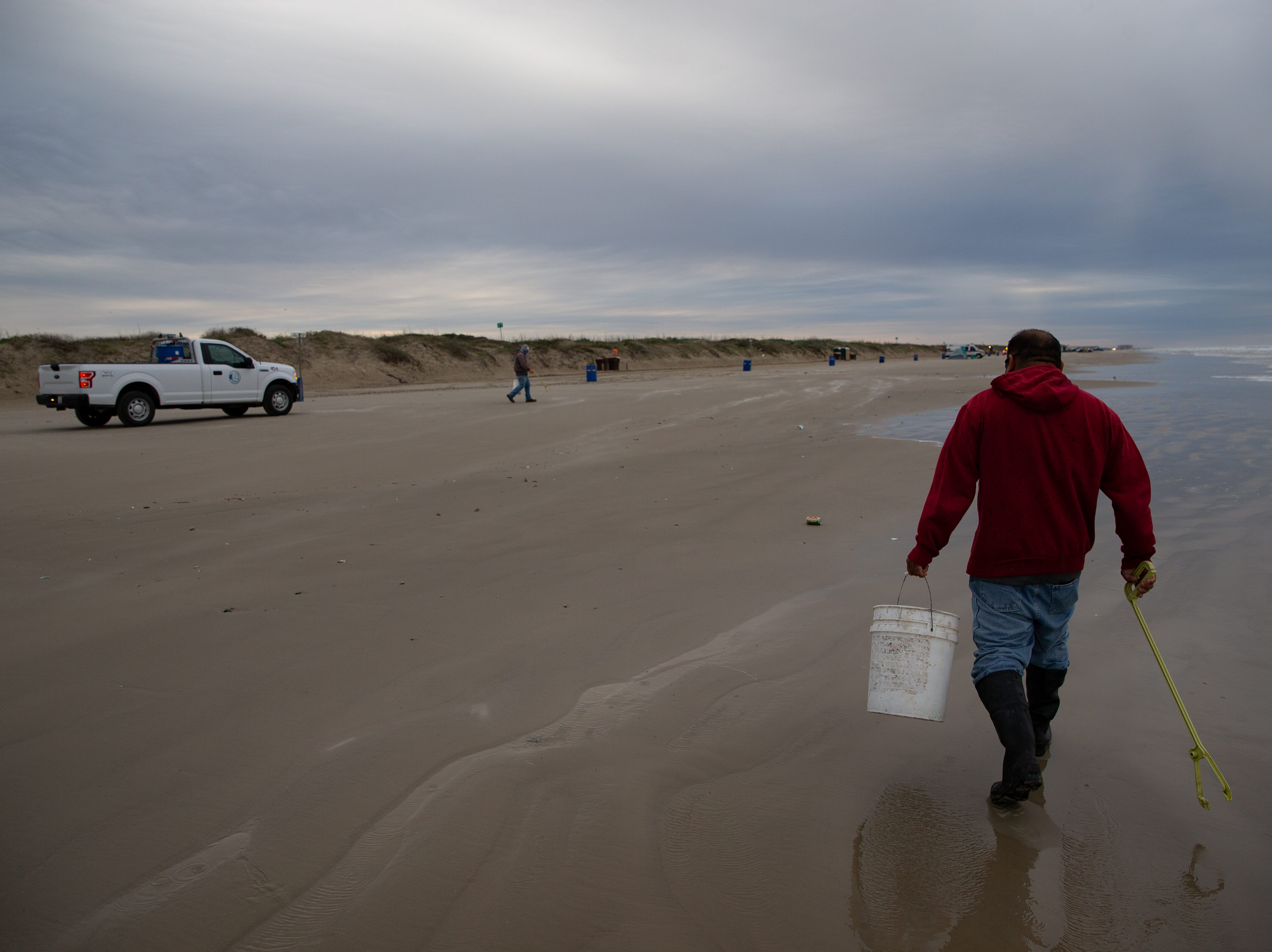 Port Aransas sanitation workers in the early morning collecting trash left on the beach from the bay before during the week of spring break on Friday, March 15, 2019.