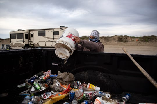 A Port Aransas sanitation worker in the early morning dumps trash collected on the beach left behind form the day before during the week of spring break on Friday, March 15, 2019.