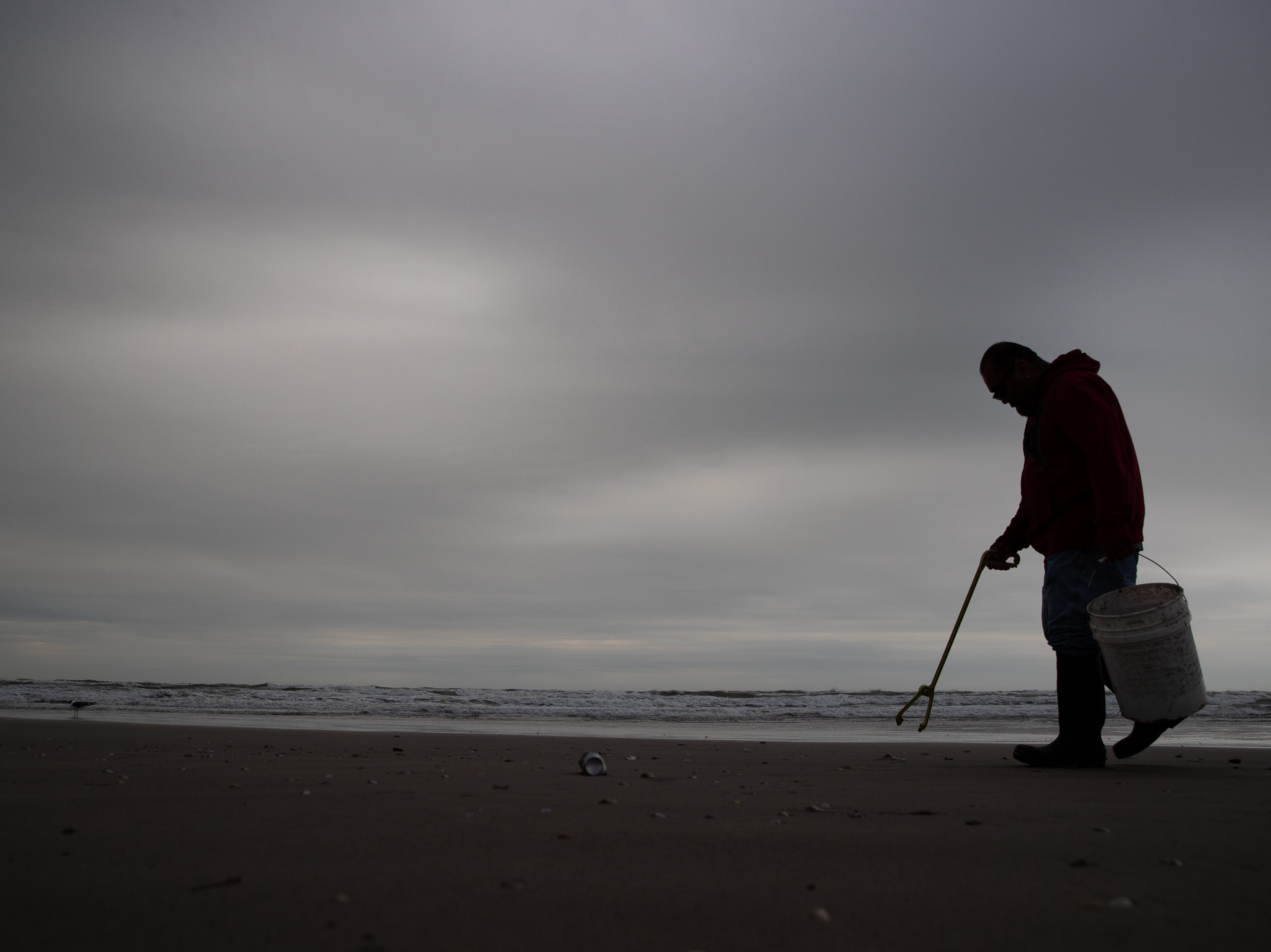 A Port Aransas sanitation worker walks the beach in the early morning collecting trash left behind form the day before during the week of spring break on Friday, March 15, 2019.