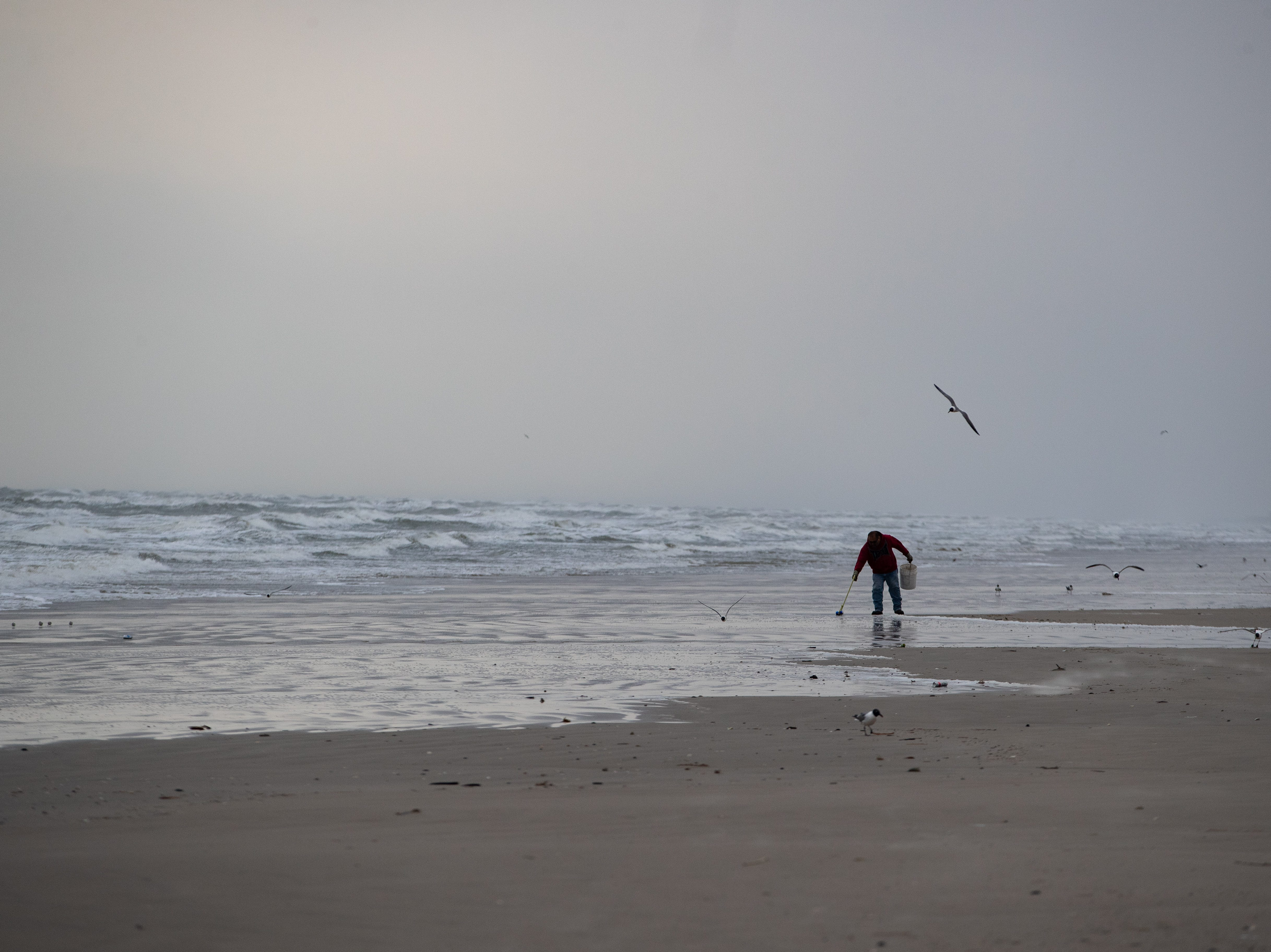 A Port Aransas sanitation worker walks the beach in the early morning collecting trash left behind from the day before during the week of spring break on Friday, March 15, 2019.