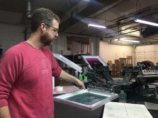 Adam Woods, CEO of Camden Printworks, shows how to silkscreen designs onto shirts. The South Camden business was burglarized sometime recently, with machines, supplies and computers stolen.