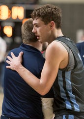 Adena senior Zach Fout hugs coach Kyle Bradley during the fourth quarter of Adena's Division III regional semifinal game against Harvest Prep at Ohio University's Convocation Center on March 14, 2019.