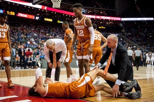 Texas Longhorns head coach Shaka Smart and Texas Longhorns guard Kerwin Roach II (12) check on Texas Longhorns forward Jaxson Hayes (10) after an injury during the second half of the quarterfinals of the Big 12 conference tournament at Sprint Center on March 14.