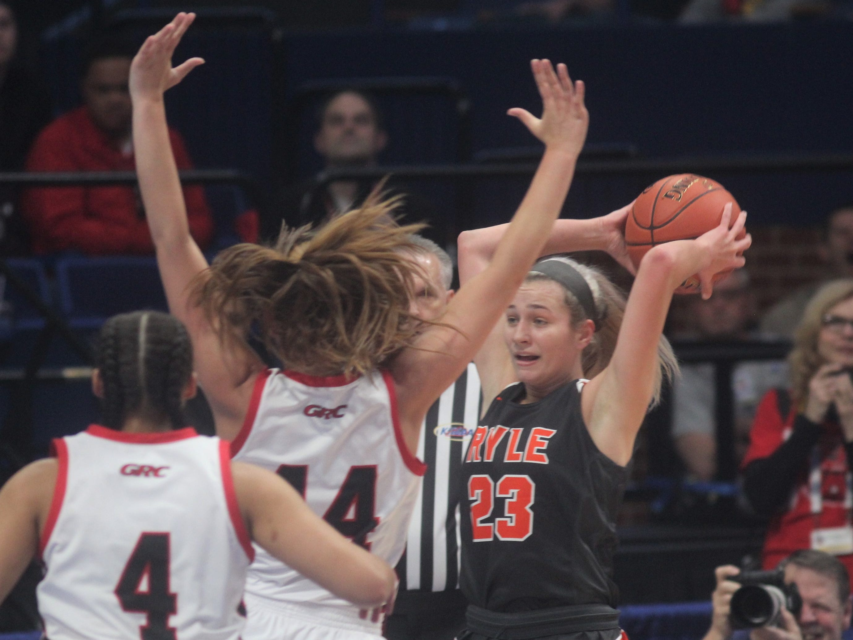 Ryle junior Maddie Scherr passes over GRC's Hayley Harrison as Ryle defeated George Rogers Clark 64-51 in the state quarterfinals of the KHSAA Sweet 16 girls basketball tournament March 15, 2019 at Rupp Arena, Lexington KY.