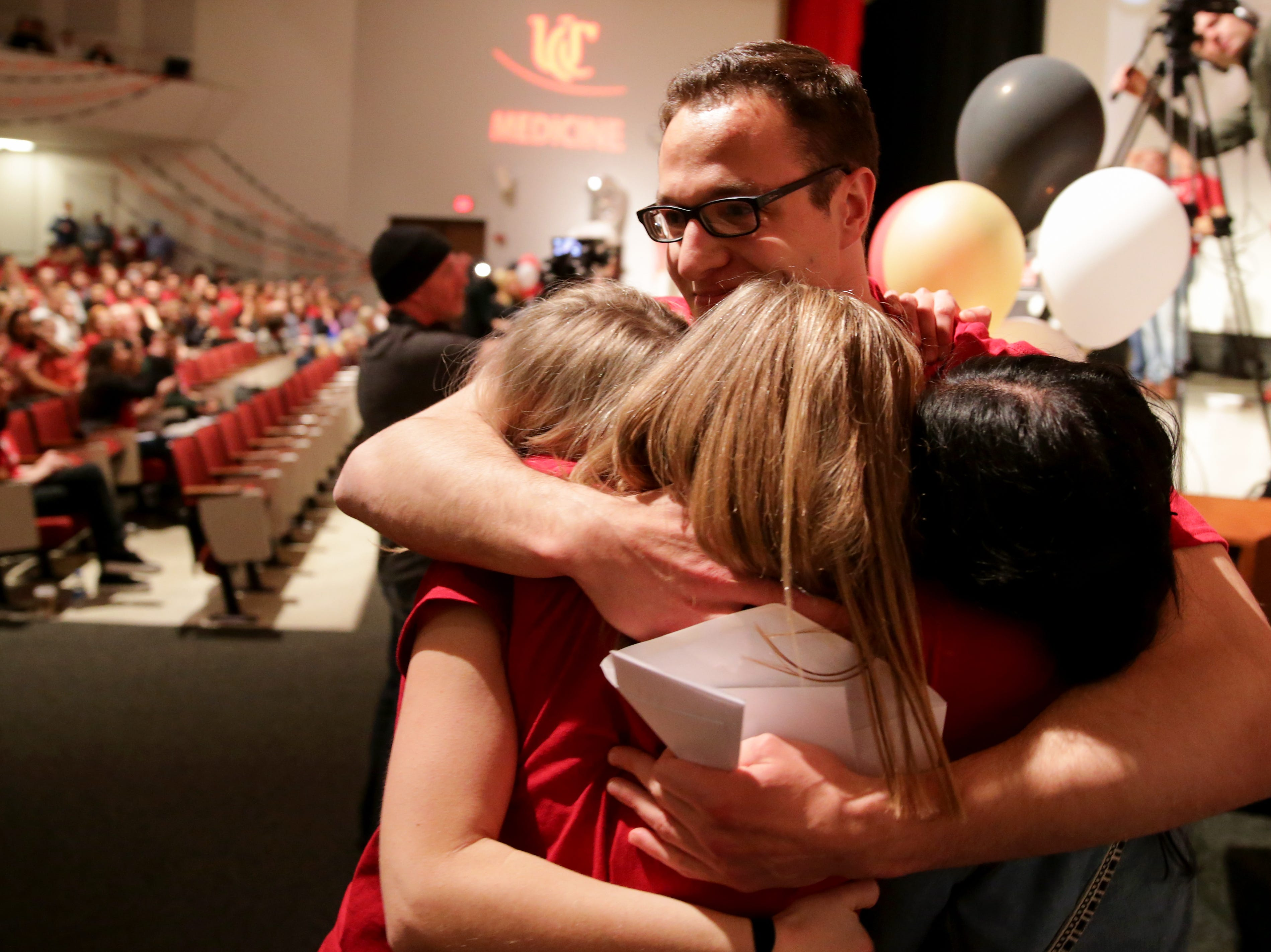 Karl Greenblatt hugs three of his classmates during Match Day, Friday, March 15, 2019, at the University of Cincinnati's College of Medicine.
