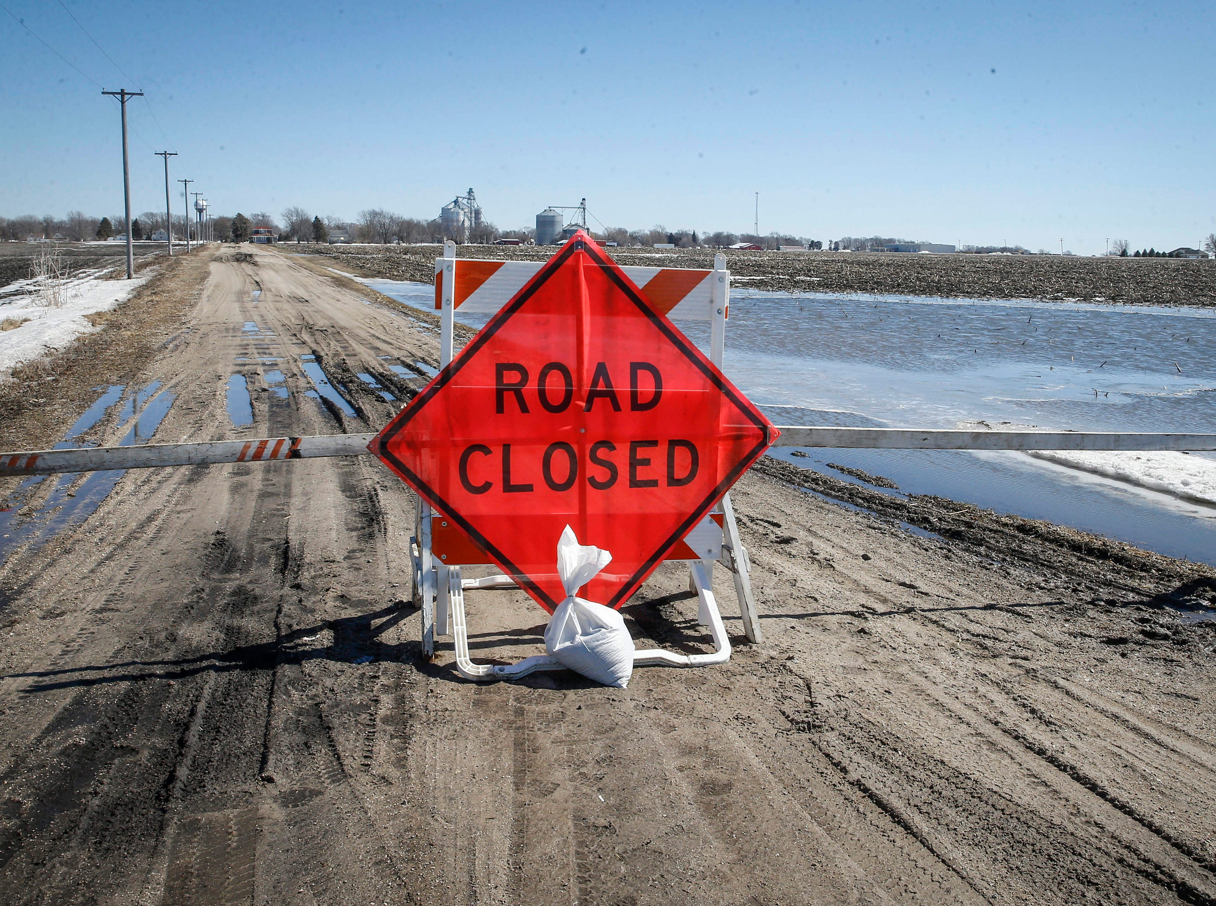 Water from melting snow has caused counties in Iowa to close some secondary roads, like this road in Stratford in Hamilton County, on Friday, March 15, 2019.