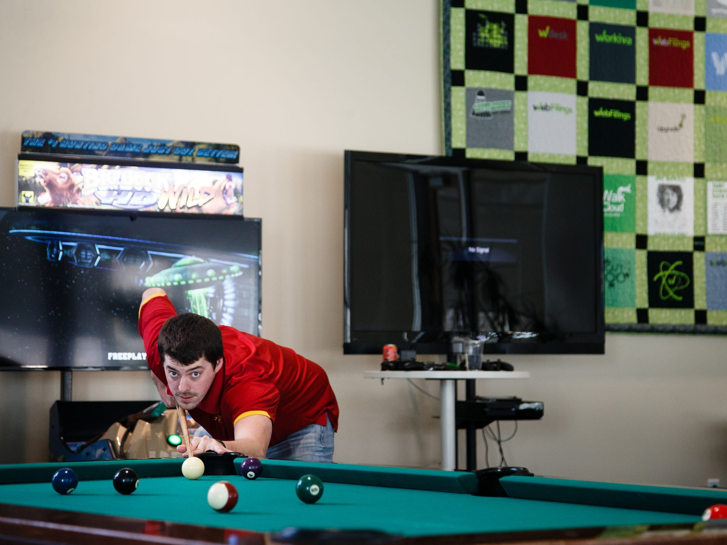 Kyle Swenson, 28 of Ames, takes a break from work to play a game of pool at Workiva, a tech company in Ames, on Friday, March 15, 2019.