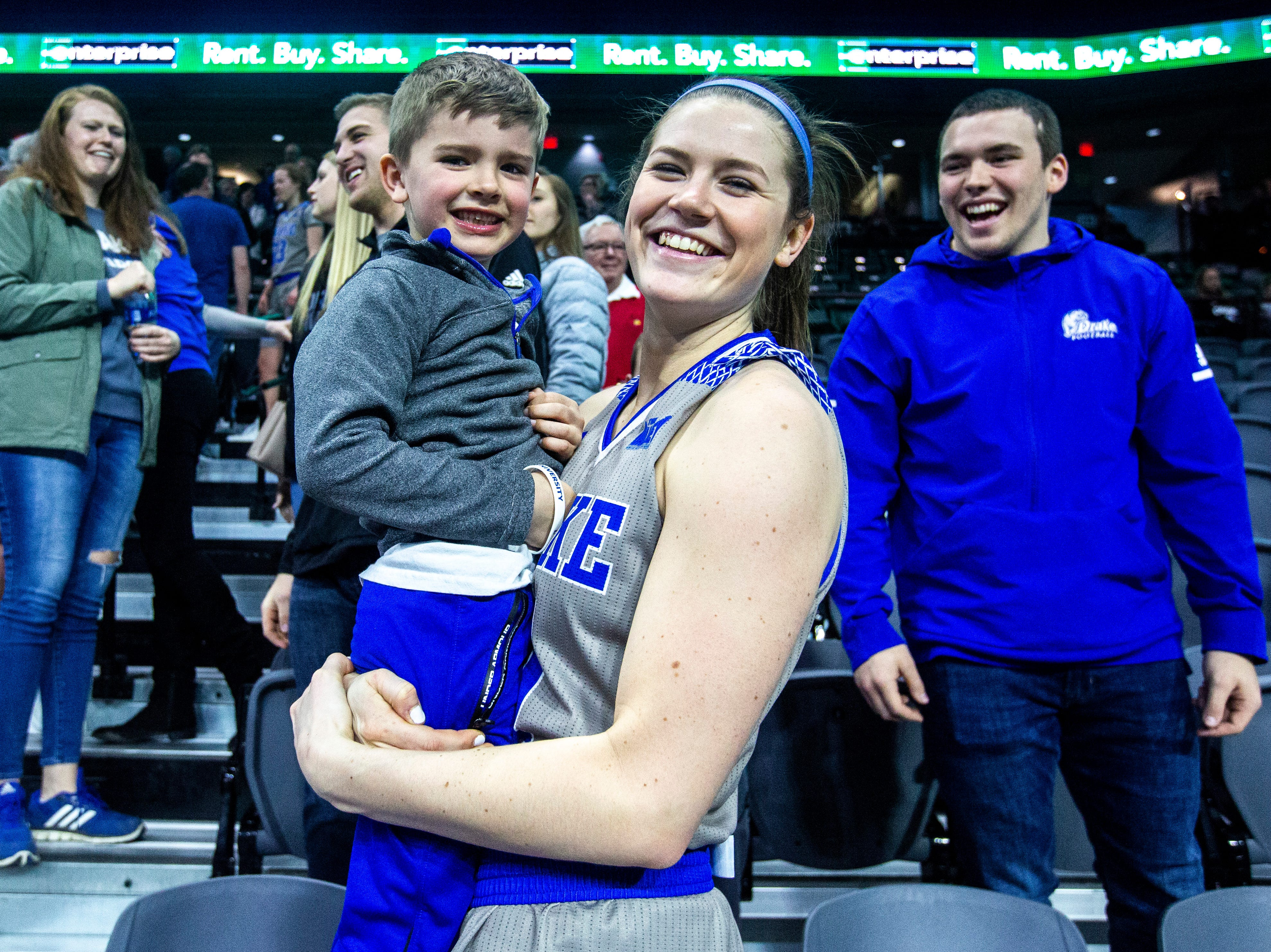 Drake guard Sammie Bachrodt (21) celebrates with family and friends as Drake running back Drew Lauer, right, laughs after a NCAA Missouri Valley Conference women's basketball quarterfinal tournament game, Friday, March 15, 2019, at the TaxSlayer Center in Moline, Illinois.