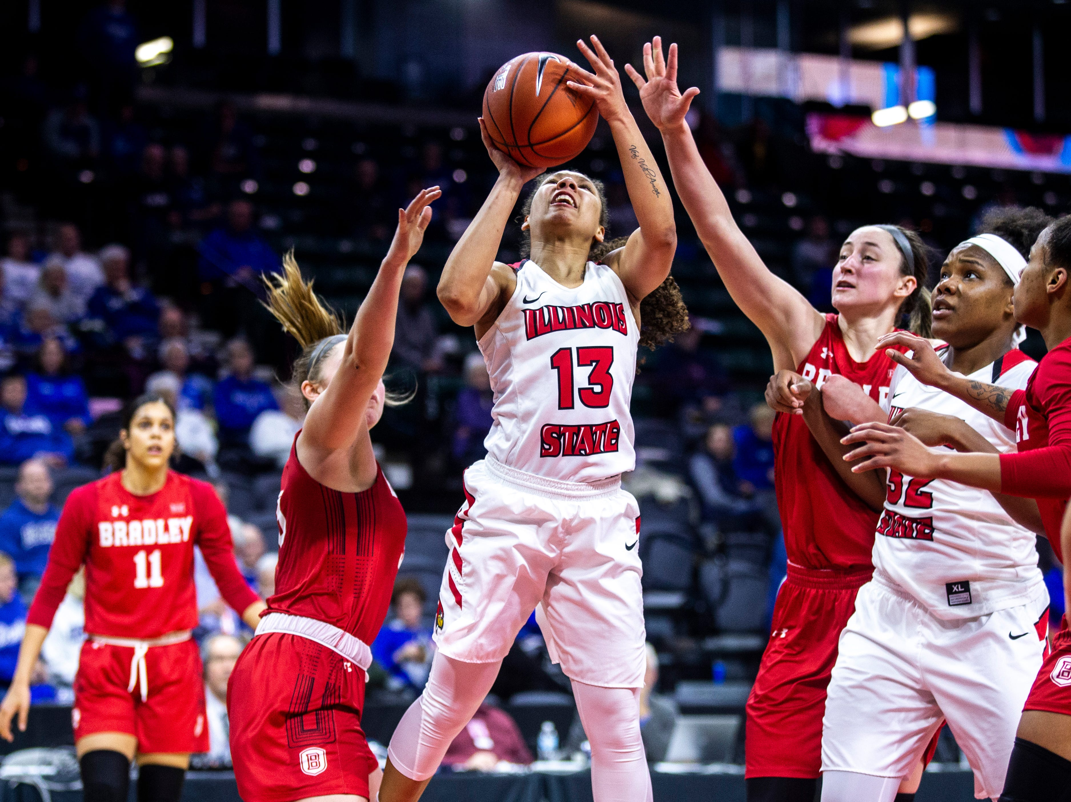 Illinois State guard Katrina Beck (13) drives to the basket while drawing a foul from Bradley guard Gabi Haack, second from left, during a NCAA Missouri Valley Conference women's basketball quarterfinal tournament game, Friday, March 15, 2019, at the TaxSlayer Center in Moline, Illinois.