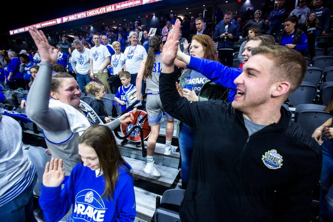 Drake tight end and basketball fan Cole Neary, right, high-fives Drake guard Maddy Dean (20) after a NCAA Missouri Valley Conference women's basketball quarterfinal tournament game, Friday, March 15, 2019, at the TaxSlayer Center in Moline, Illinois.