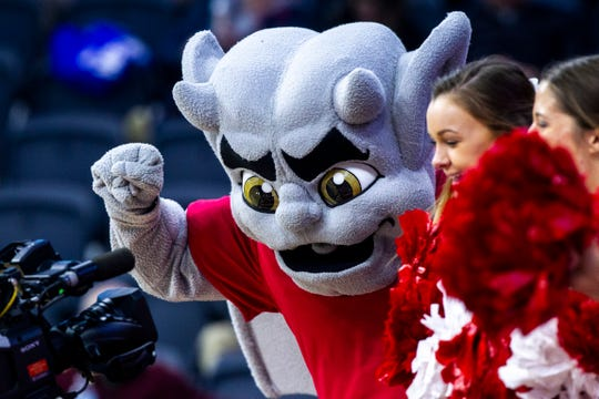 """""""Kaboom!"""" the gargoyle, Bradley's mascot, plays to a camera with cheerleaders during a NCAA Missouri Valley Conference women's basketball quarterfinal tournament game, Friday, March 15, 2019, at the TaxSlayer Center in Moline, Illinois."""