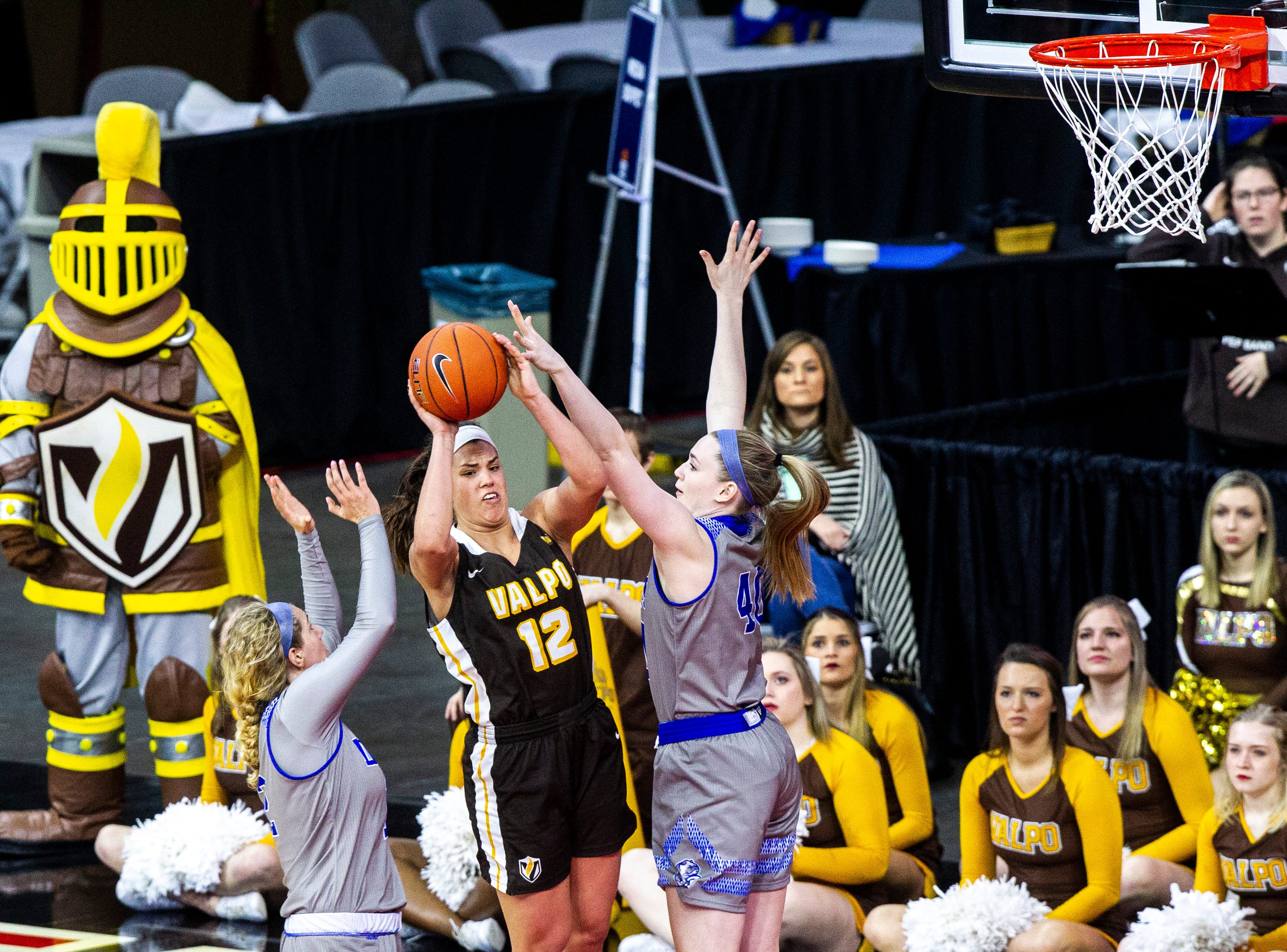 Valparaiso's Addison Stoller (12) gets defended by Drake's Mya Mertz, right, and Drake's Brenni Rose, left, during a NCAA Missouri Valley Conference women's basketball quarterfinal tournament game, Friday, March 15, 2019, at the TaxSlayer Center in Moline, Illinois.