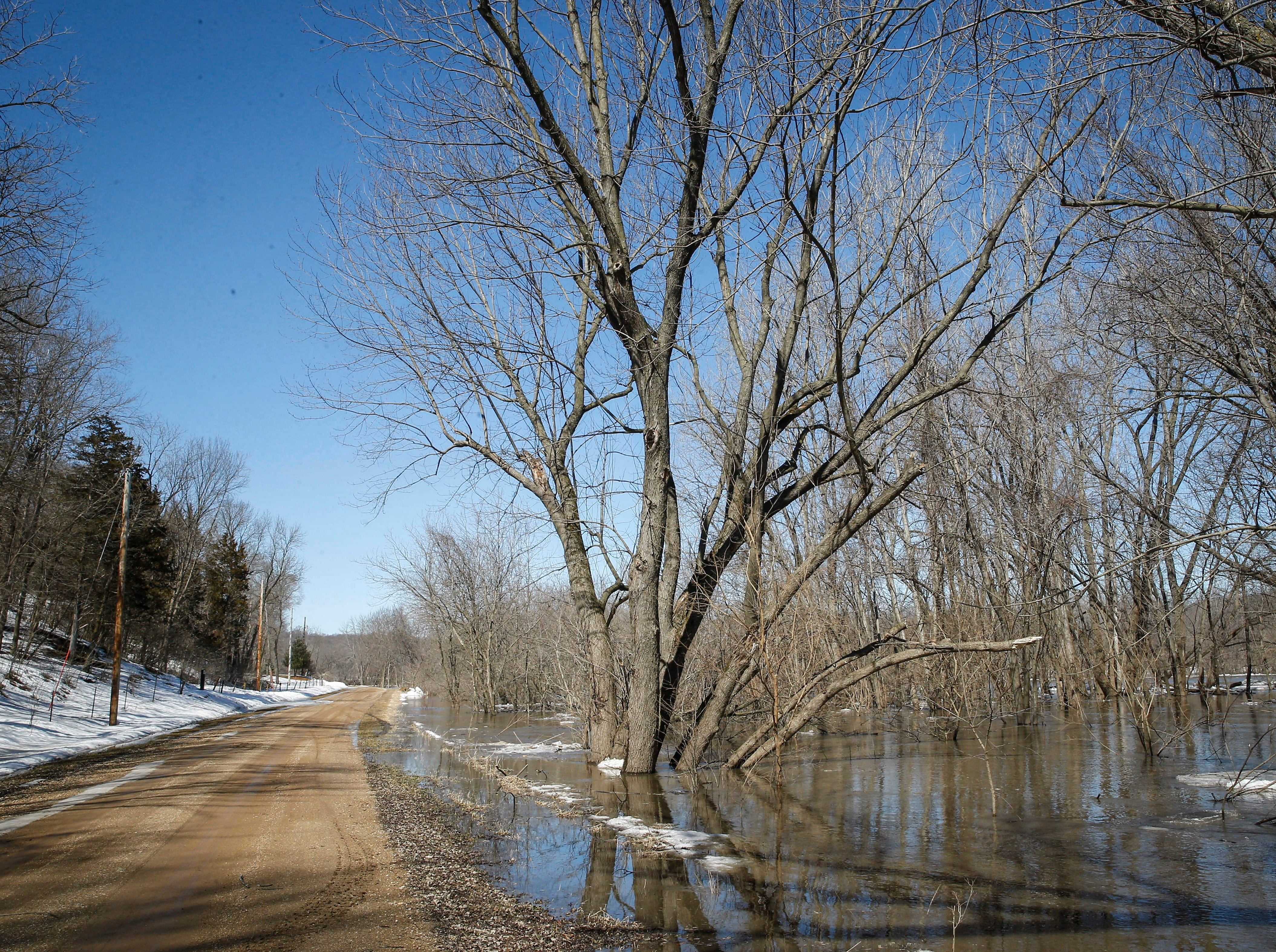 Water from the swollen Des Moines River threatens to cross over River Road near Stratford in Hamilton County  on Friday, March 15, 2019.