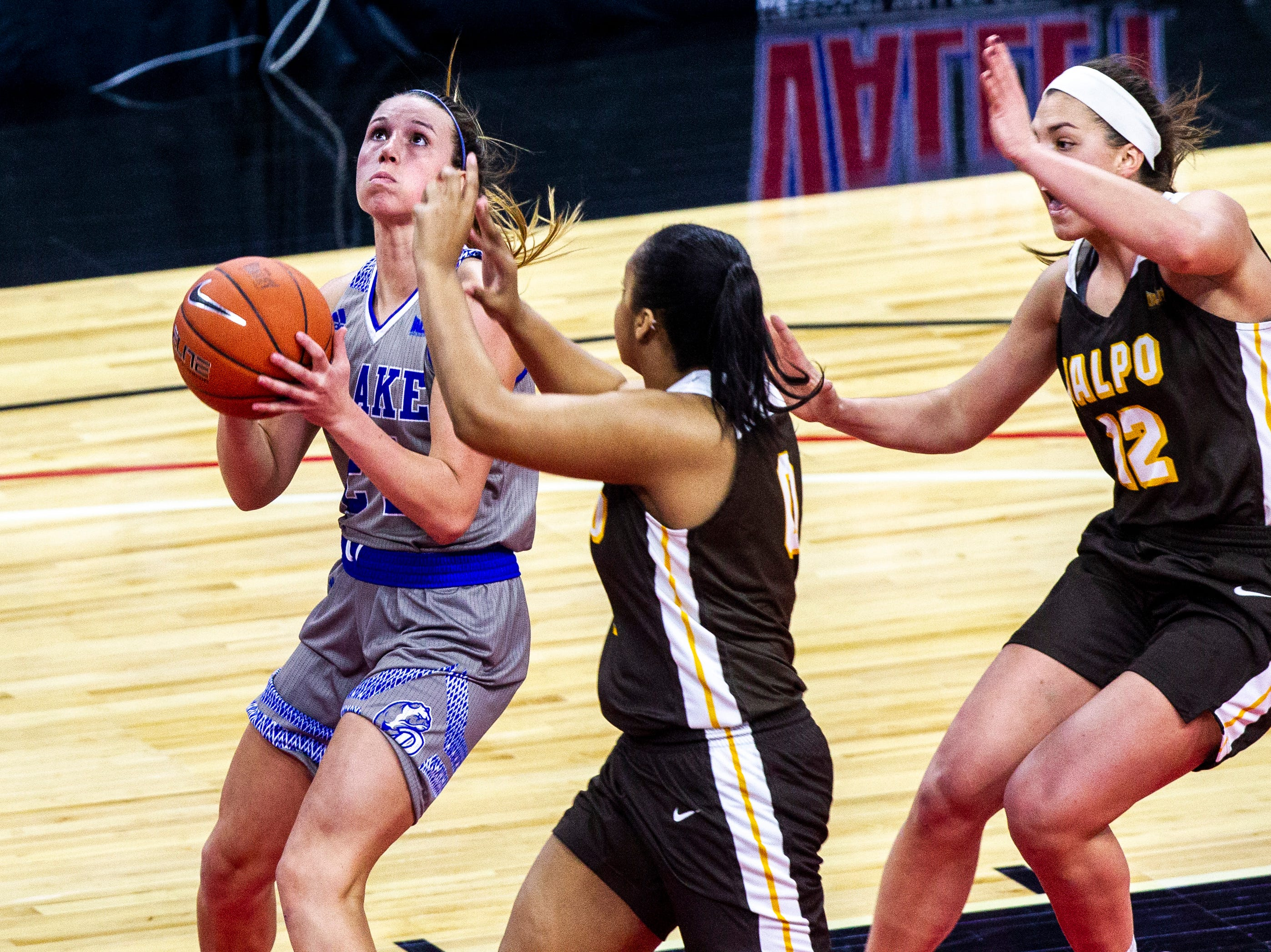 Drake guard Nicole Miller (24) drives to the basket past Valparaiso guard Maya Meredith, center, and Valparaiso's Addison Stoller (12) during a NCAA Missouri Valley Conference women's basketball quarterfinal tournament game, Friday, March 15, 2019, at the TaxSlayer Center in Moline, Illinois.