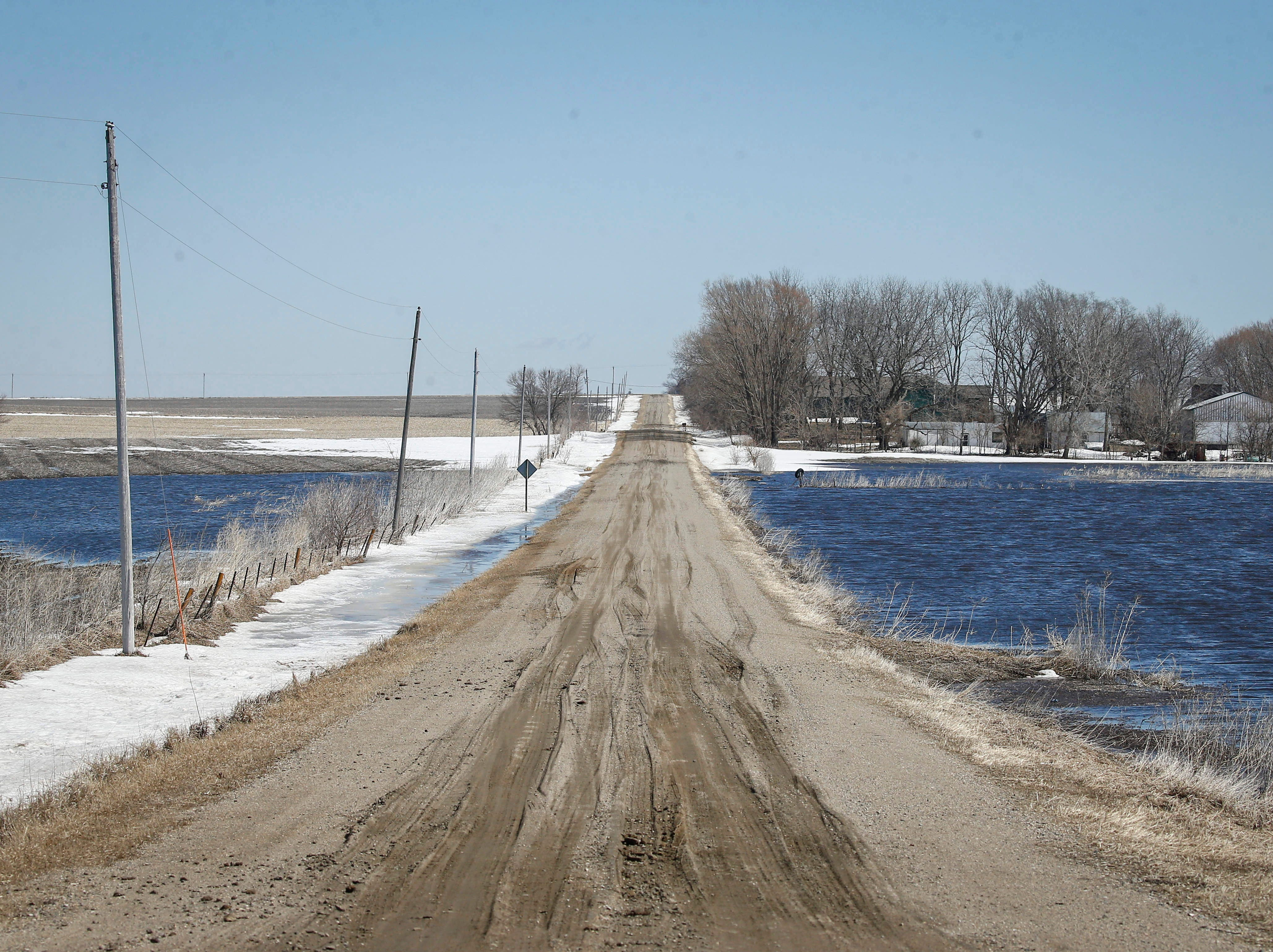 Water from melting snow inches close to 400th Street near Stratford in Hamilton County, on Friday, March 15, 2019.