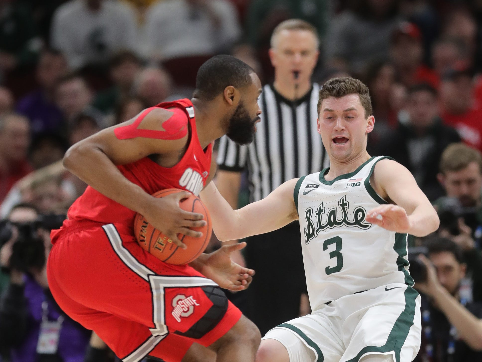 Michigan State's Foster Loyer takes the charge against Ohio State's Keyshawn Woods during the first half of the Big Ten tournament Friday, March 15, 2019 at the United Center in Chicago.