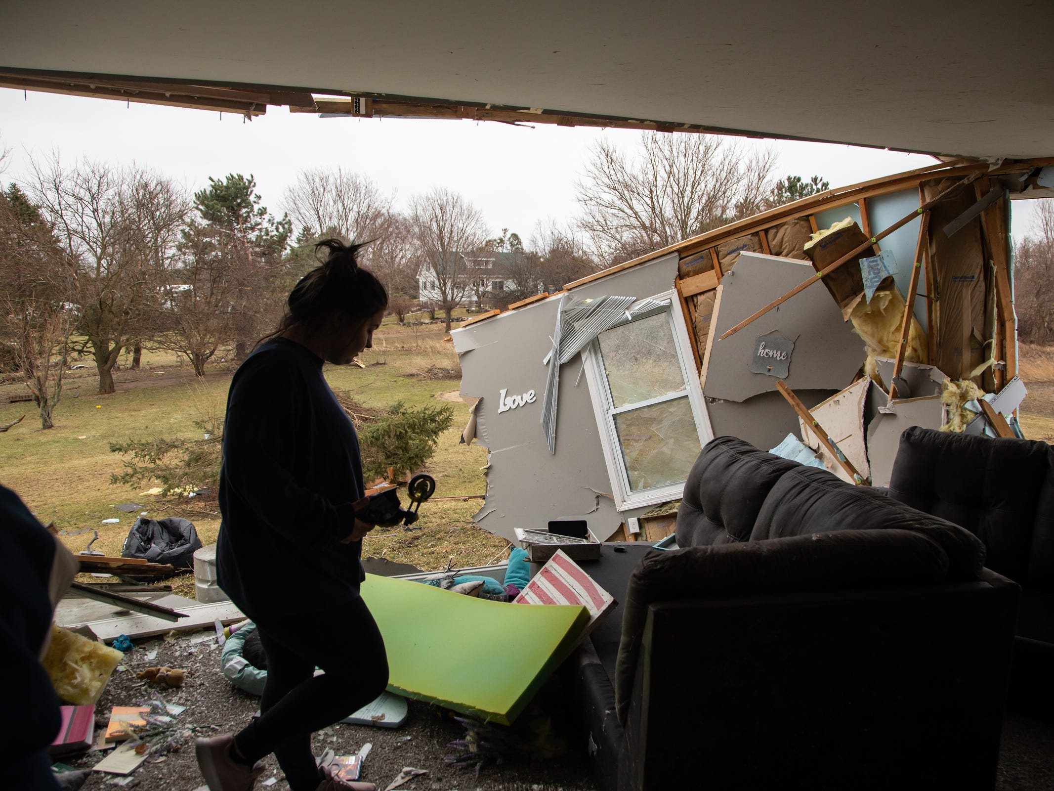 """Mackenzie Weaver helps clear items from the living room area of her mother's home in Bancroft on Friday, March 15, 2019 that was damaged after a tornado moved through Shiawassee County overnight. """"When I came to the house today I wasn't expecting it to be as bad as it really is. It freaked me out it really did. I was crying hysterically. I called in to work today so I could help them out,"""" Weaver said.Weavers mother and her six foster children were in the house at the time of the tornado hitting and got a call from her mother-in-law to get in the basement seconds before it hit. No one was injured but two goats and a chicken died in the storm."""