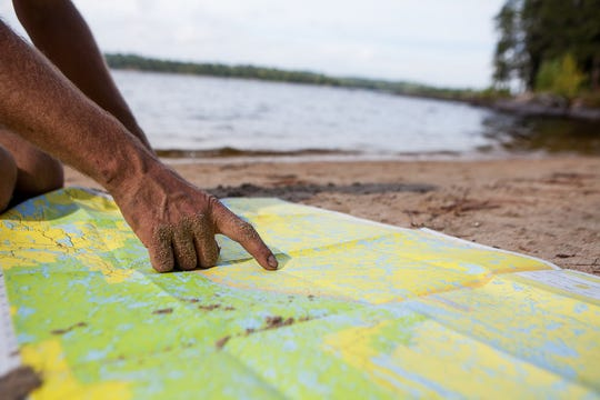 Porter Fox consults a depth chart of MinnesotaÕs Boundary Waters while canoeing the border between Canada and the lower 48 United States.
