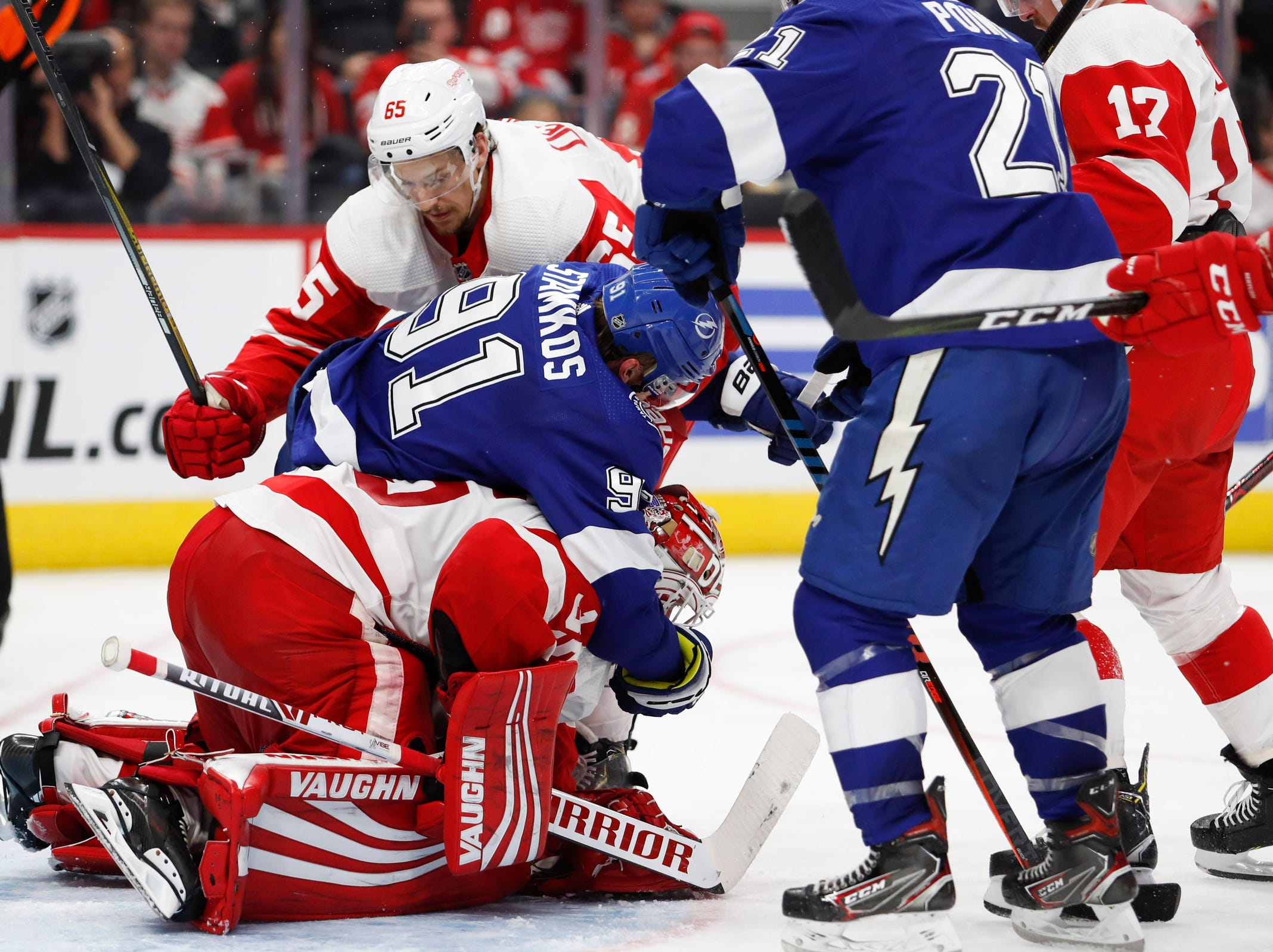 Lightning center Steven Stamkos falls on the back of Red Wings goaltender Jimmy Howard as he is defended by defenseman Danny DeKeyser during the third period of the Wings' 5-4 loss to the Lightning on Thursday, March 14, 2019, at Little Caesars Arena.