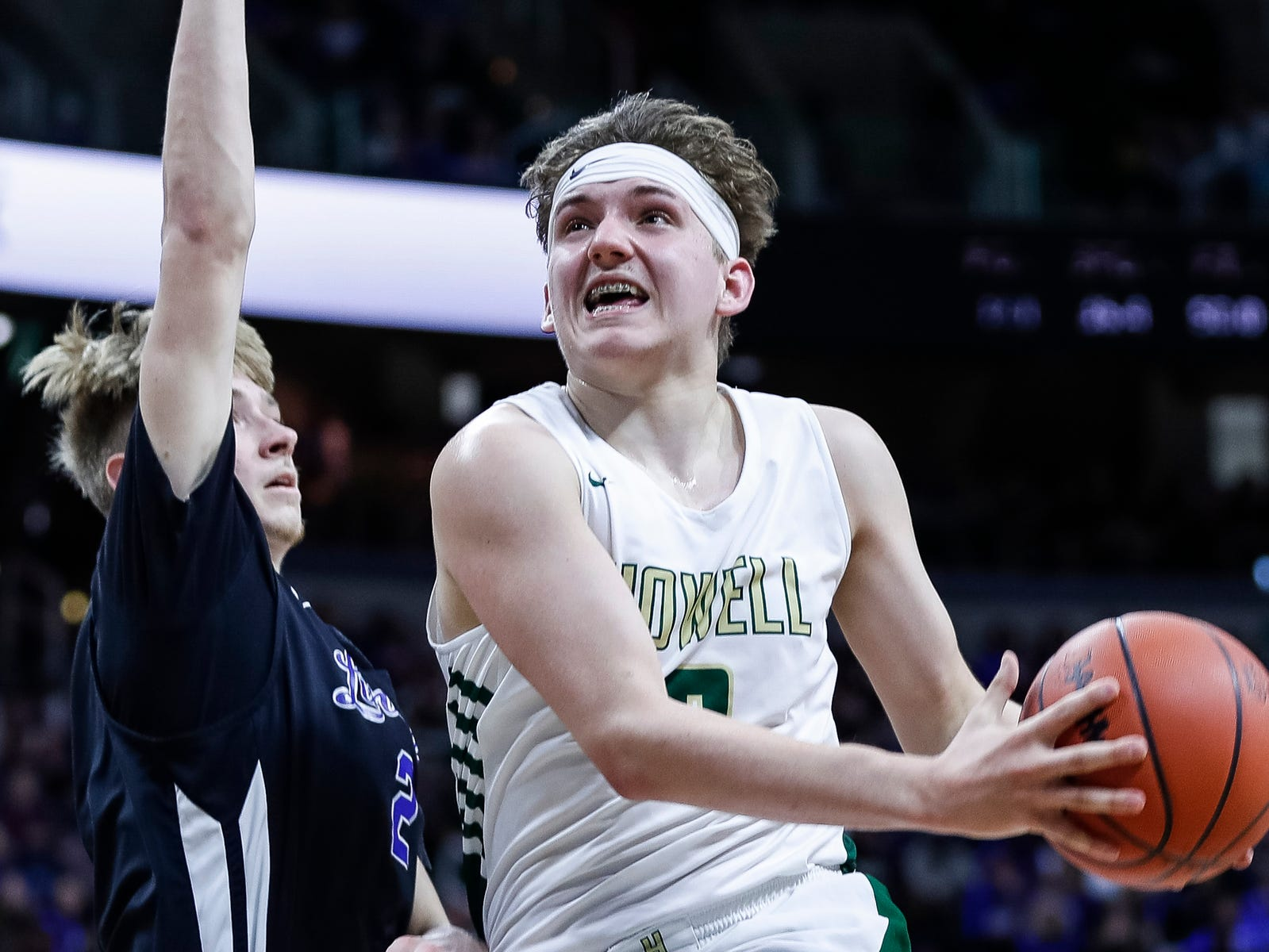 Howell's Josh Palo (0) makes a layup against Ypsilanti Lincoln's Cameron Johnson (2) during the second  half of MHSAA Division 1 semifinal at the Breslin Center in East Lansing, Friday, March 15, 2019.
