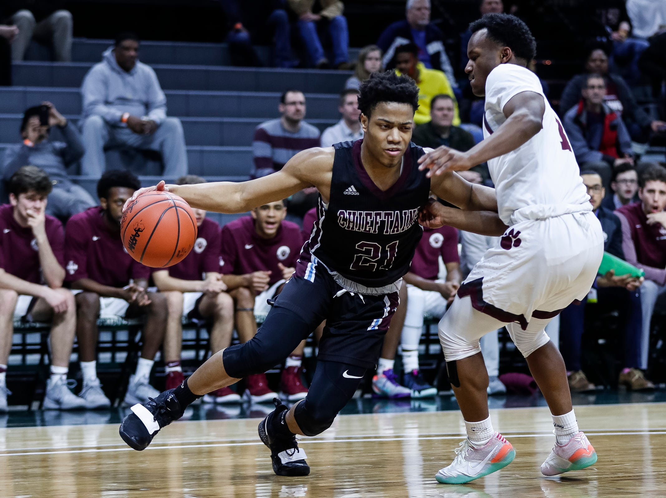 Okemos' Noah Pruitt (21) is defended by U-D Jesuit's Julian Dozier (1) during the first half of MHSAA Division 1 semifinal at the Breslin Center in East Lansing, Friday, March 15, 2019.