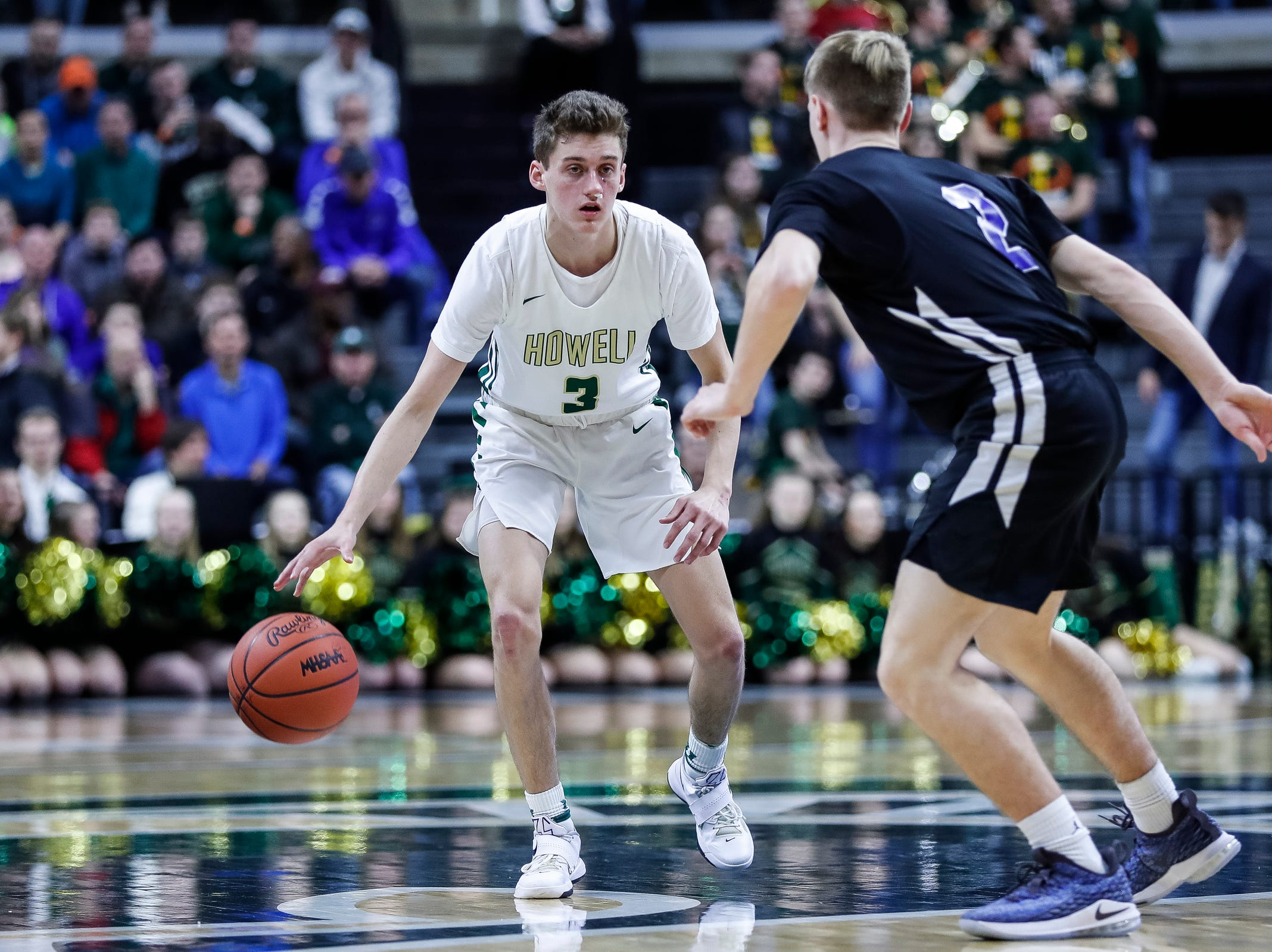 Howell's Kip French (3) dribbles against Ypsilanti Lincoln's Cameron Johnson (2) during the first half of MHSAA Division 1 semifinal at the Breslin Center in East Lansing, Friday, March 15, 2019.