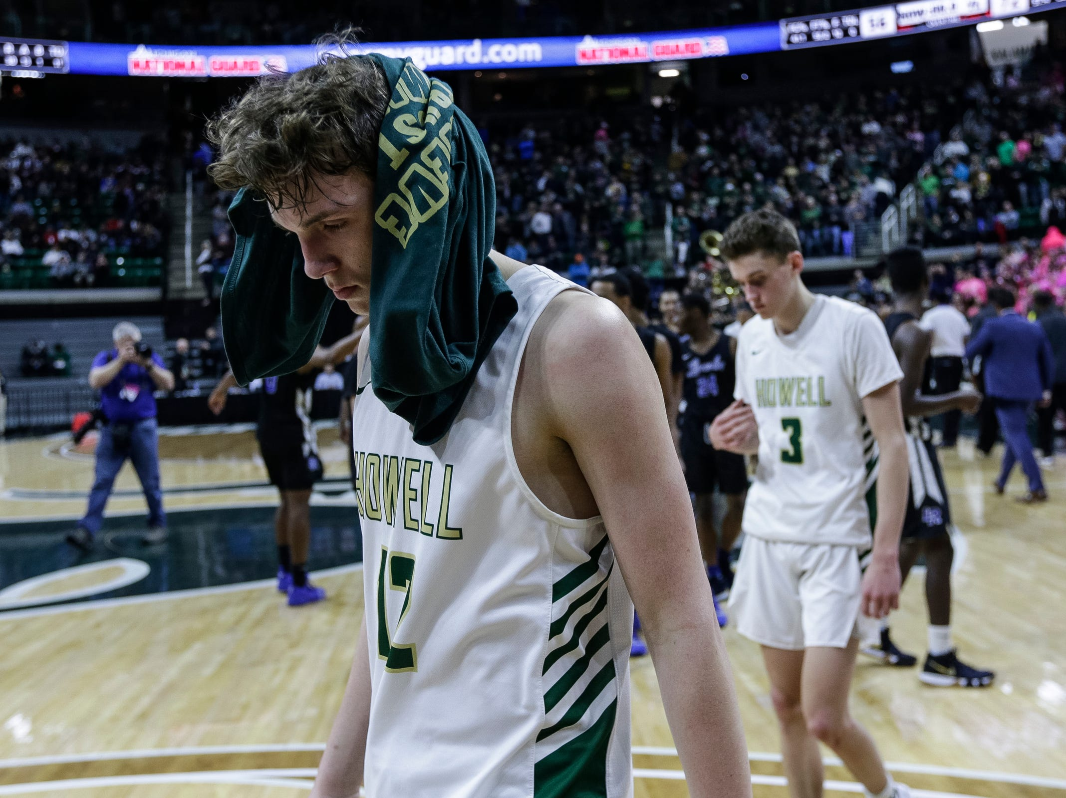 Howell's Tony Honkala (12) walks off the court with his head covered after the Highlanders lost 72-56 to Ypsilanti Lincoln at MHSAA Division 1 semifinal at the Breslin Center in East Lansing, Friday, March 15, 2019.