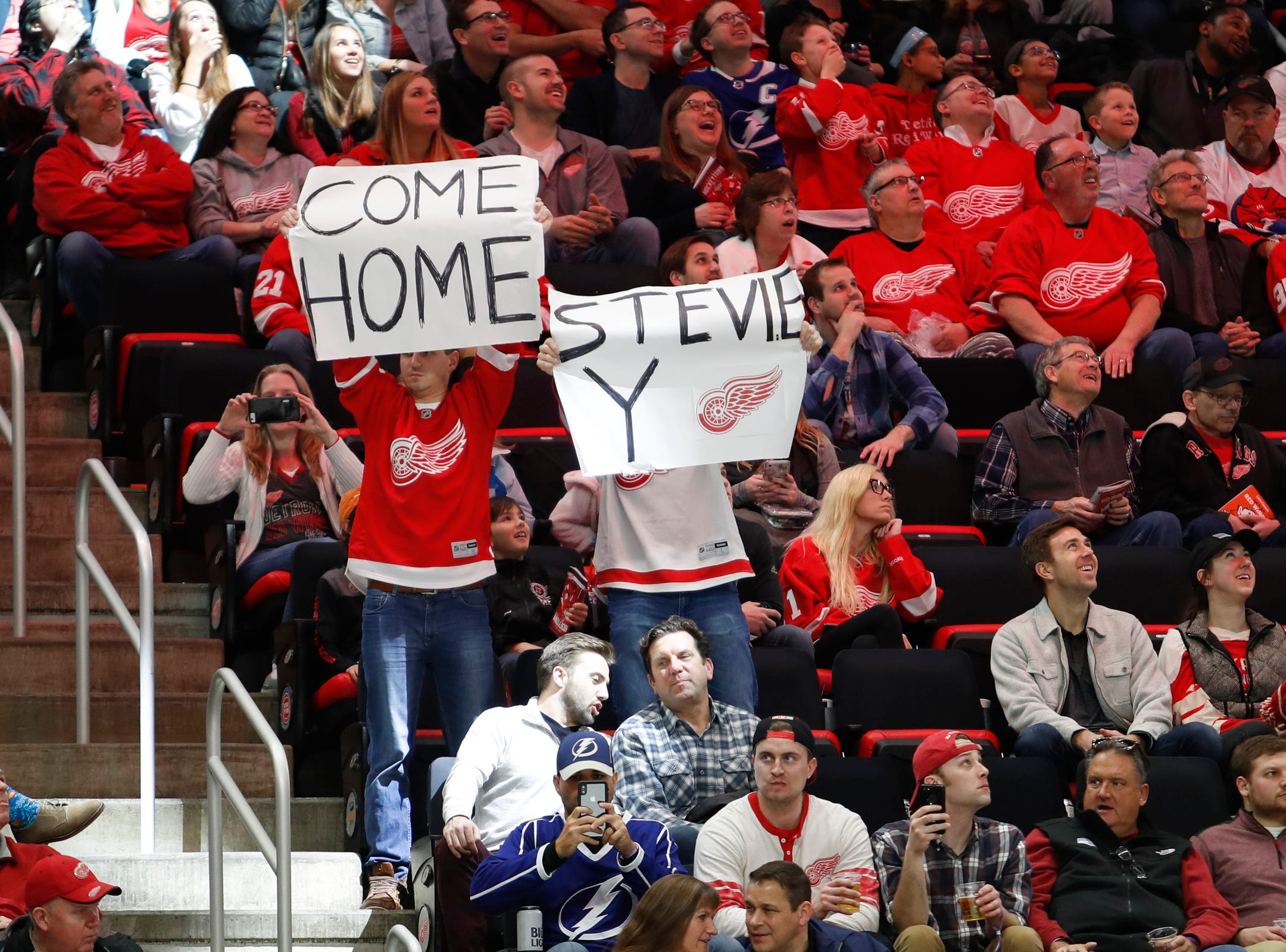 Red Wings fans hold up signs during the third period of the Wings' 5-4 loss to the Lightning on Thursday, March 14, 2019, at Little Caesars Arena.