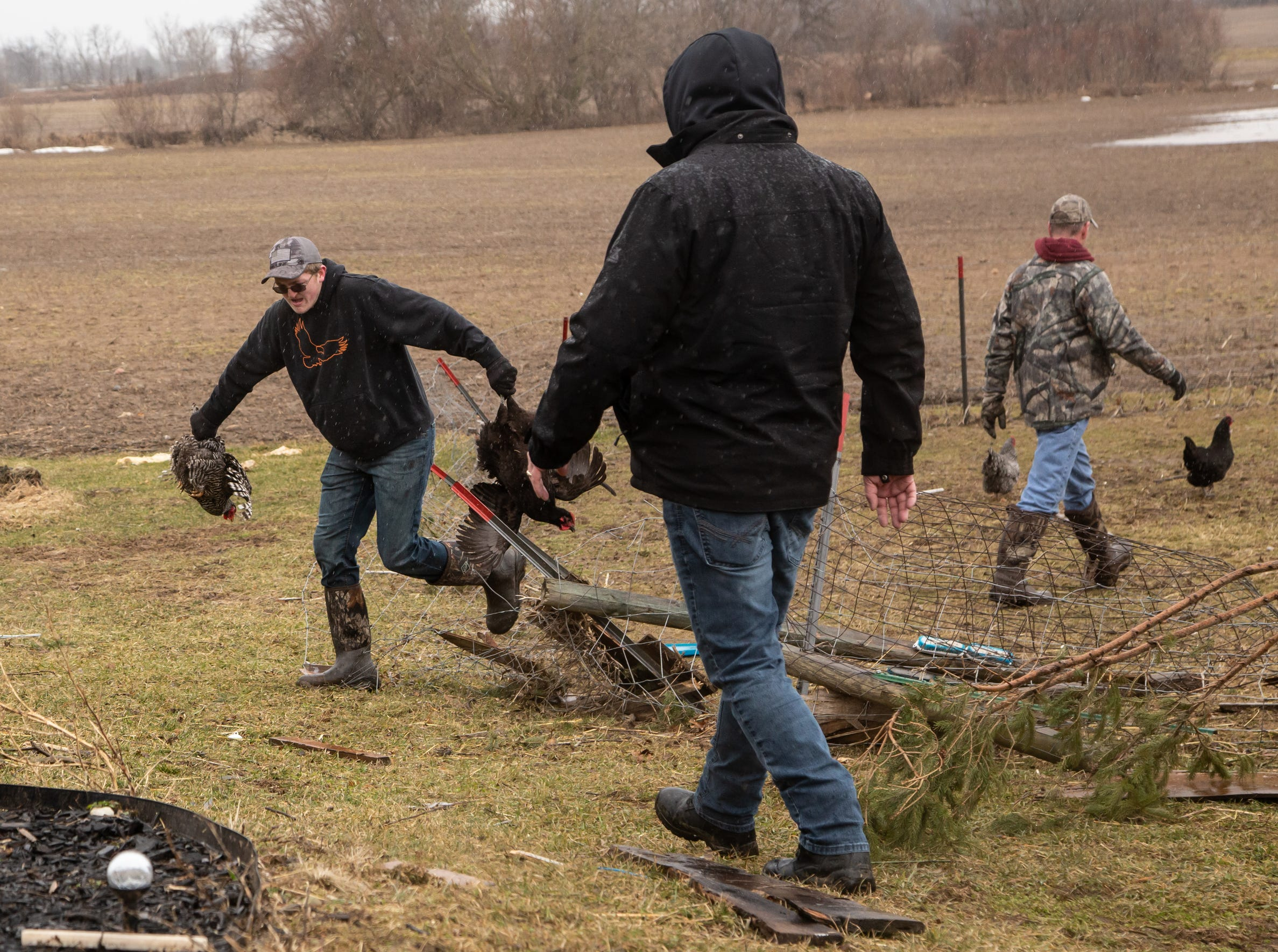 Dawson Terwilliger (left) of Grand Blanc helps wrangle chicken at a home in Bancroft on Friday, March 15, 2019 after a tornado through Shiawassee County overnight. The chickens were loose after the coup was destroyed and garage and house were damaged at the home of Bobbiejo Bruff. Two goats and a chicken were killed in the storm.