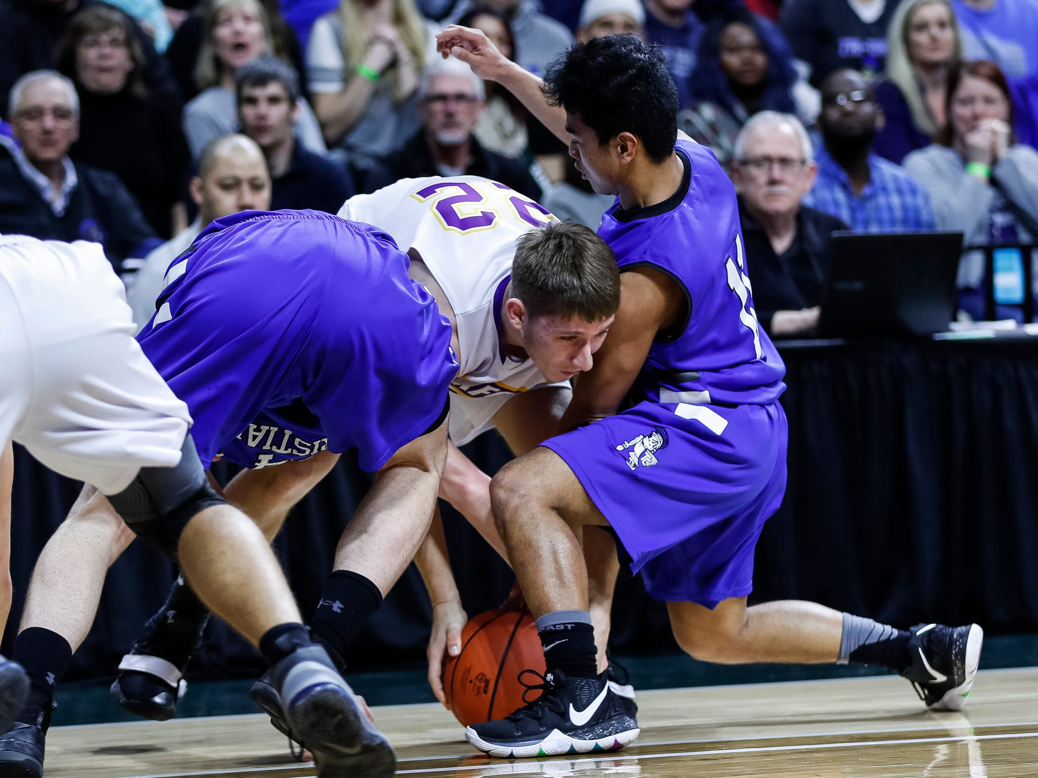 Frankfort's Ethan Ness (22) battle for the loose ball with Wyoming Tri-unity Christian's Benson Heath (11) during the first half of MHSAA Division 4 semifinal at the Breslin Center in East Lansing, Thursday, March 14, 2019.