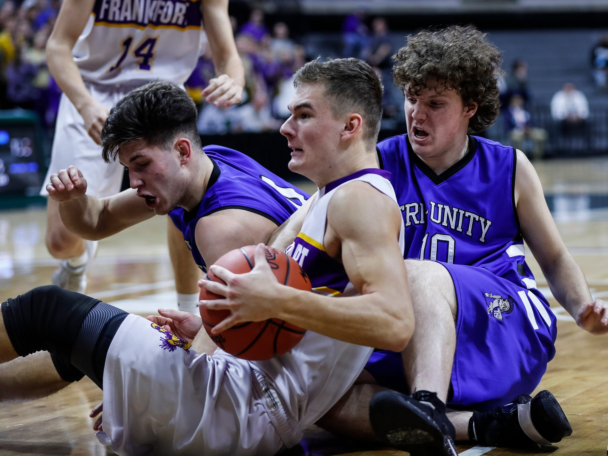 Frankfort's Conner Smith (15) battle for the loose ball with Wyoming Tri-unity Christian's Brayden Ophoff (4) and Bennett Sinner (10) during the first half of MHSAA Division 4 semifinal at the Breslin Center in East Lansing, Thursday, March 14, 2019.