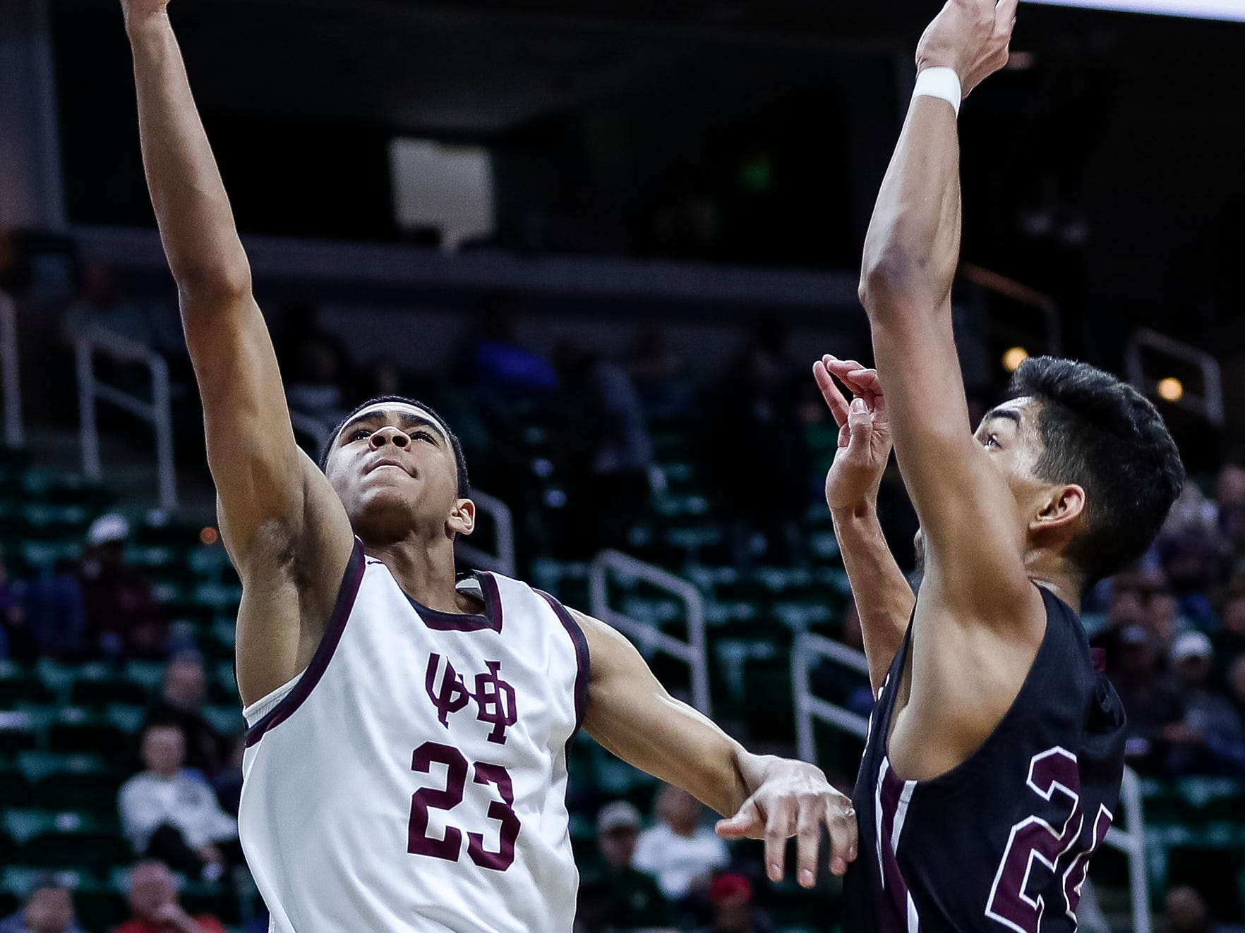 U-D Jesuit's JonMarcus Roland (23) makes a layup against Okemos' Evan Thomas (24) during the second half of MHSAA Division 1 semifinal at the Breslin Center in East Lansing, Friday, March 15, 2019.