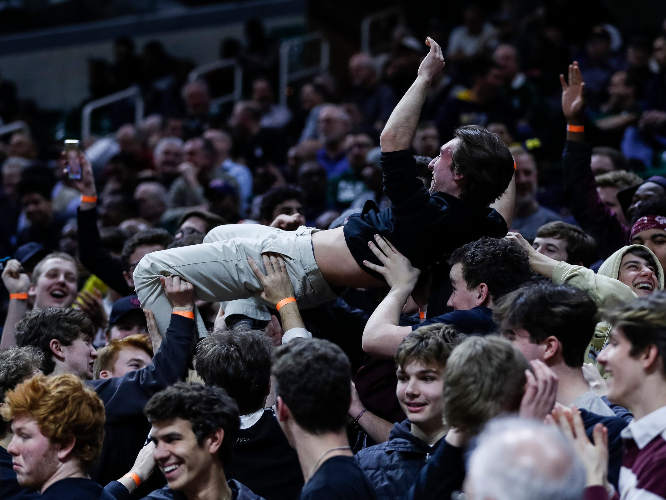 U-D Jesuit student section celebrate the Cubs big lead over Okemos during the second half of MHSAA Division 1 semifinal at the Breslin Center in East Lansing, Friday, March 15, 2019.