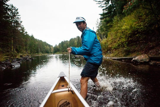 """Porter Fox, author of """"Northland: A 4,000-Mile Journey Along America's Forgotten Border,""""  pulls his canoe through some shallows in Minnesota's Boundary Waters while paddling along the boundary between Canada and the lower 48 United States."""