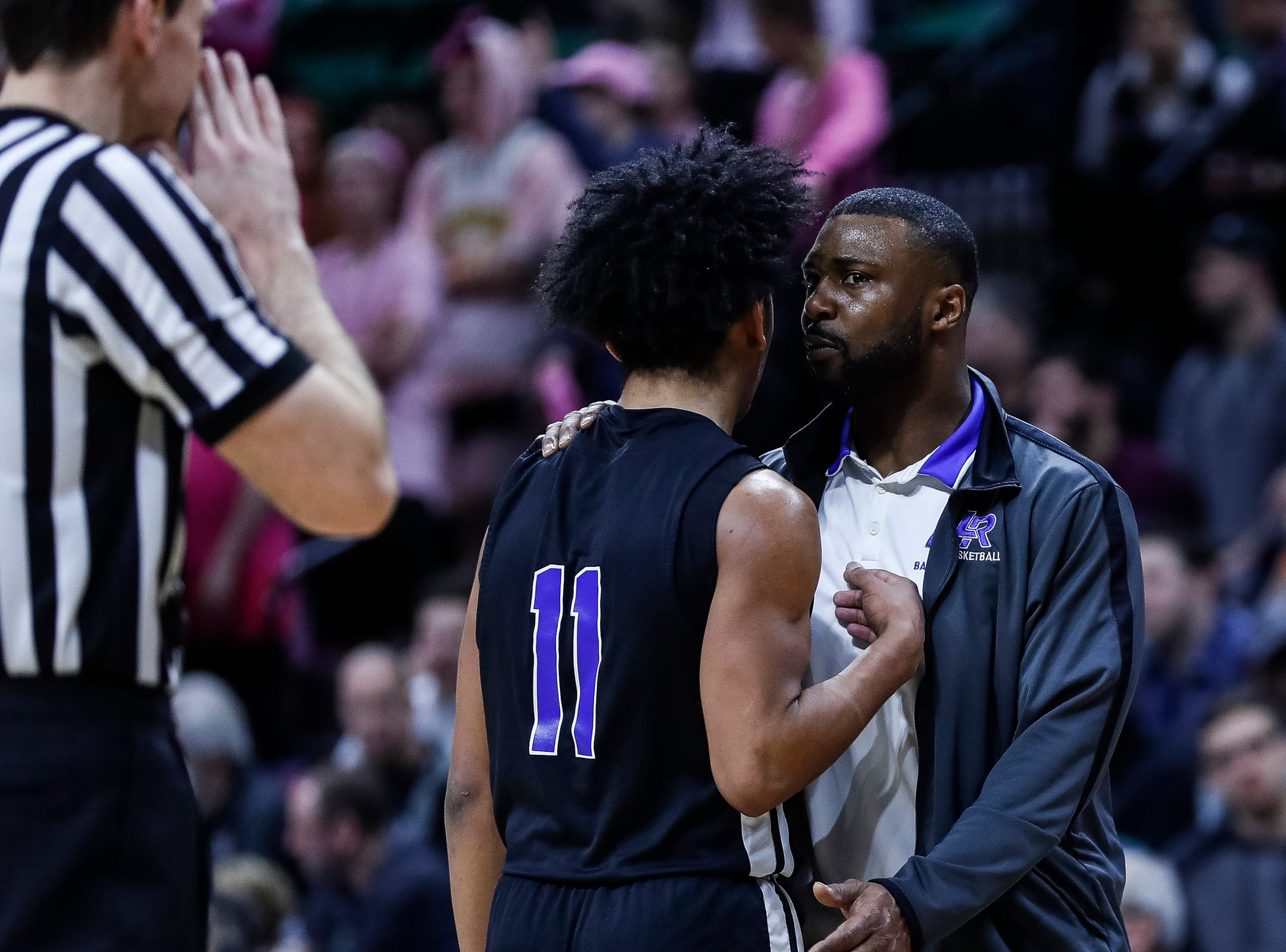 Ypsilanti Lincoln head coach Jesse Davis talks to Trevon Davis (11) at the timeout during the first half of MHSAA Division 1 semifinal against Howell at the Breslin Center in East Lansing, Friday, March 15, 2019.