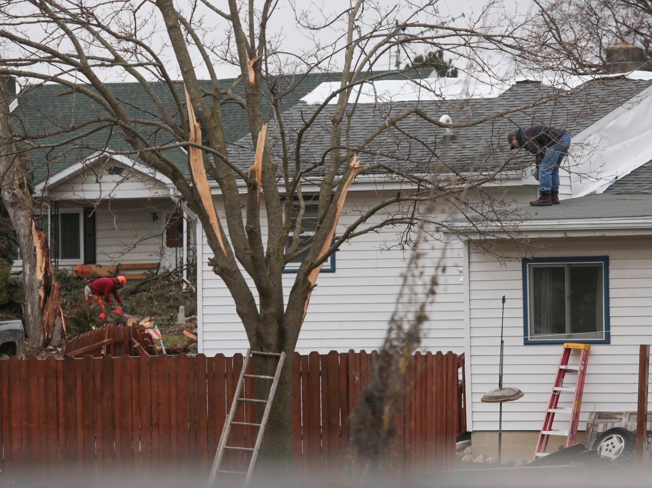 Residents work on clearing damage to yards and homes from a tornado that came through Shiawassee County overnight in Bancroft on Friday, March 15, 2019.
