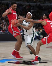 Michigan State guard Cassius Winston drives against Ohio State's  Musa Jallow and  C.J. Jackson during first half action of the Big Ten tournament Friday, March 15, 2019 at the United Center in Chicago, Ill.